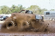 chevy mud truck driving through mud hole
