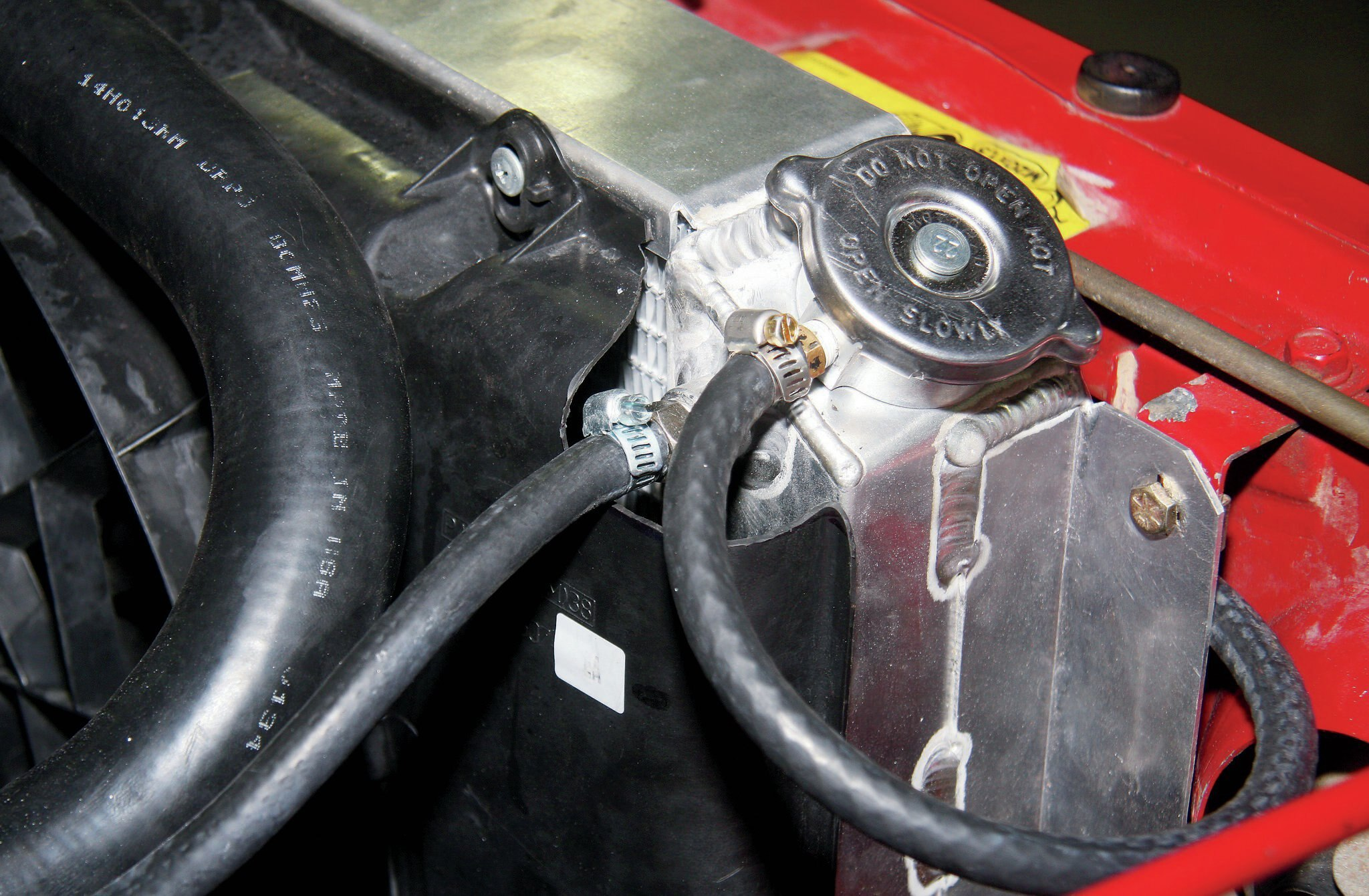 Near the radiator cap, the top hose was routed to the factory overflow bottle. The lower hose is the steam line that connects to the throttle body on these engines. The steam line is important on GM LS engines and is used to purge air from the engine coolant system and to route coolant to the throttle body.