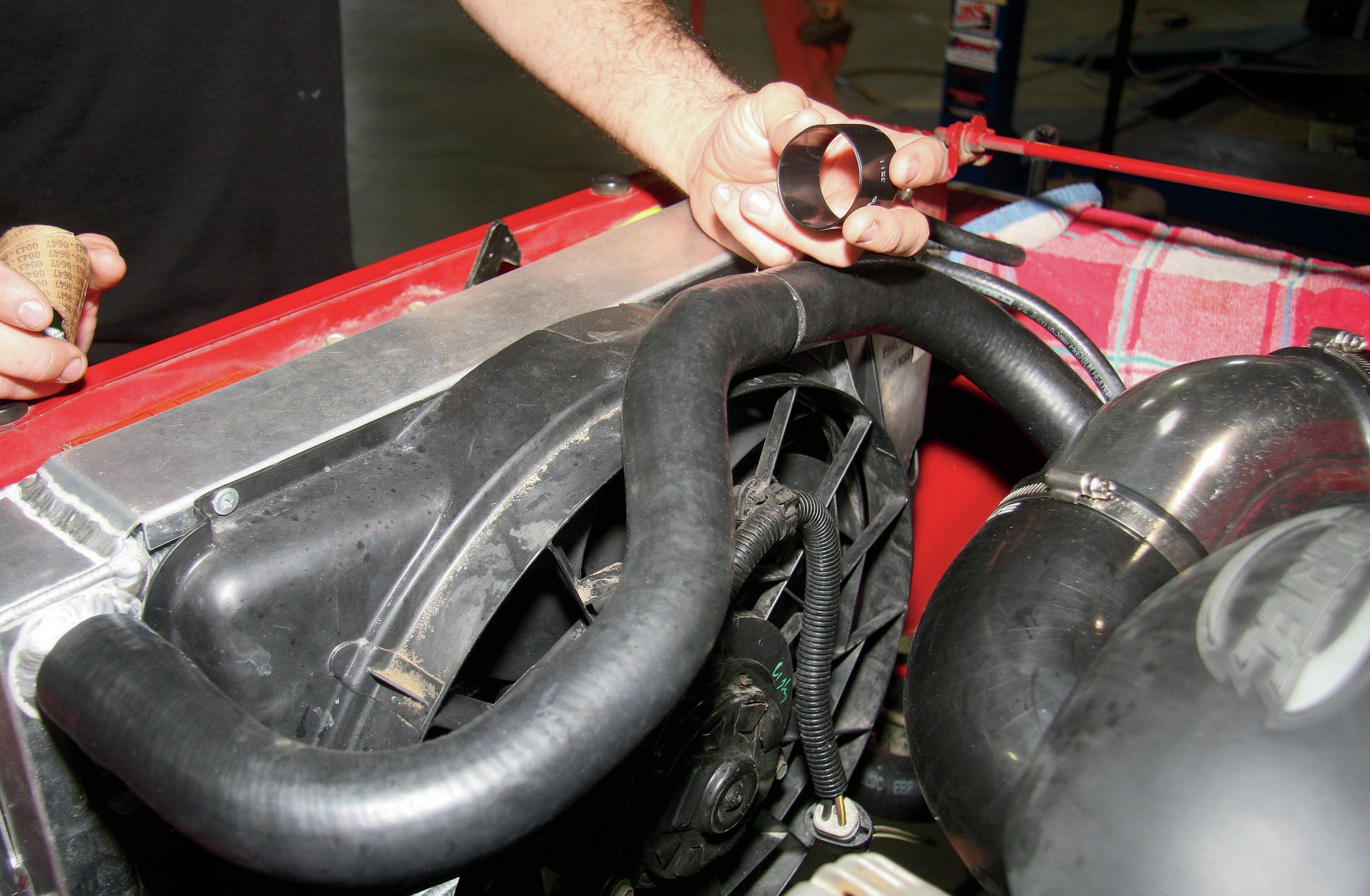 The upper hose is one used on a 5.3L Chevy truck that was cut and shortened in the middle. The two pieces were reliably and cleanly joined using a heat-shrink hose clamp. An electric fan from a Ford Taurus application was used and fits the surface area of the radiator well.