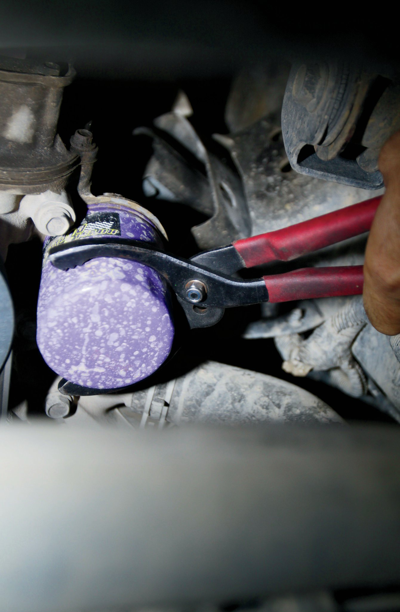 Remove the old oil filter using a small filter wrench, if necessary, and replace with the new filter. You should always lubricate the gasket on the new filter with a small amount of engine oil, as well as put some fresh oil in the filter. Due to the JK's horizontal oil filter, take care to not over fill it; otherwise, you may be taking a bath sooner than you planned. Never use a wrench or any other tool to tighten the new filter. Hand tighten only!