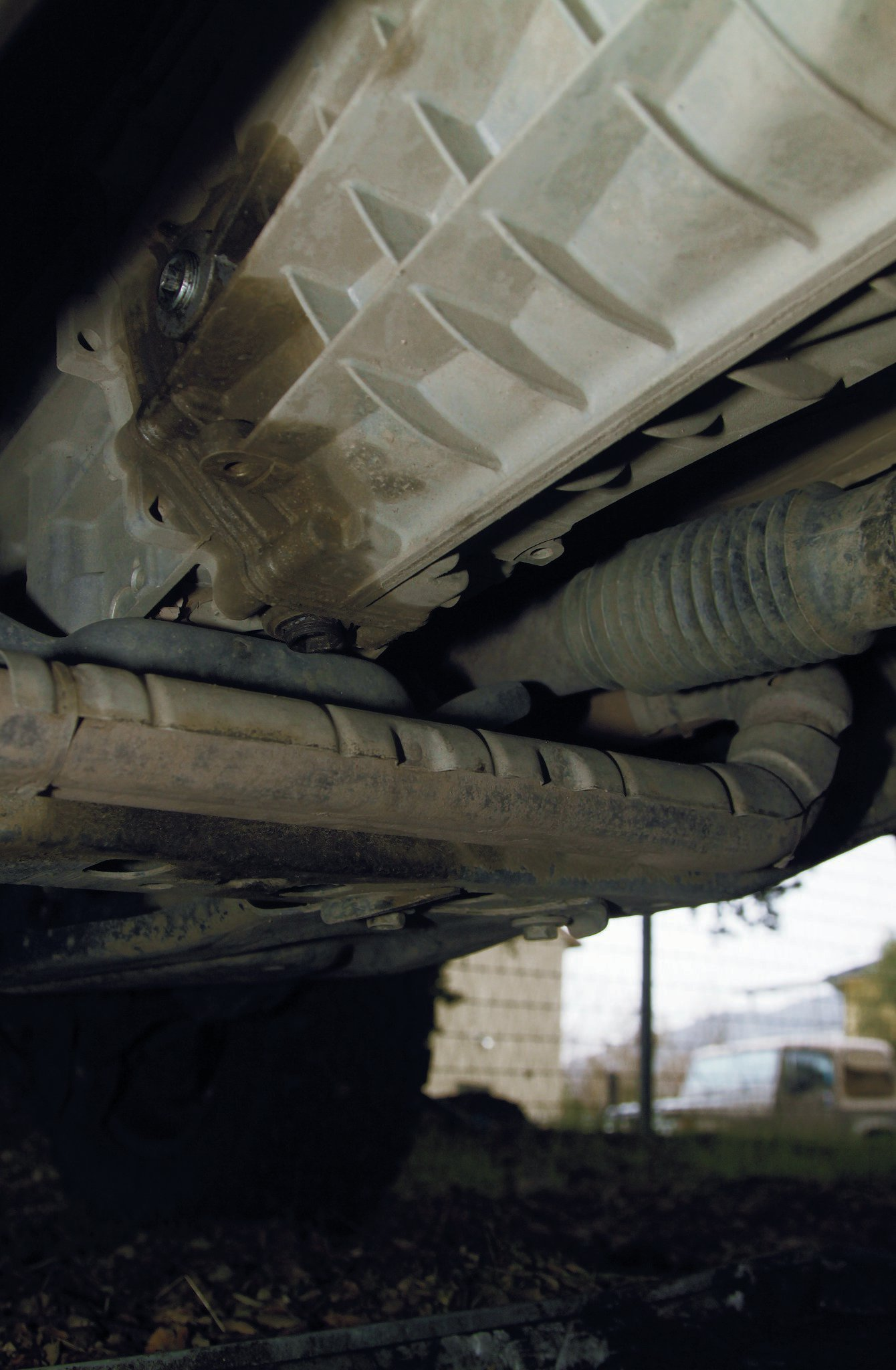 You will need to get the factory skidplate out of the way first, but the transmission and transfercase can both be drained while lying in roughly the same location. Drop the skidplate by removing the four bolts with an 18mm wrench or socket. The drain plug for the six-speed manual transmission is in a pretty bad spot, directly above the exhaust crossover. This necessitates the use of a special tool to remove the drain plug without dropping the exhaust.