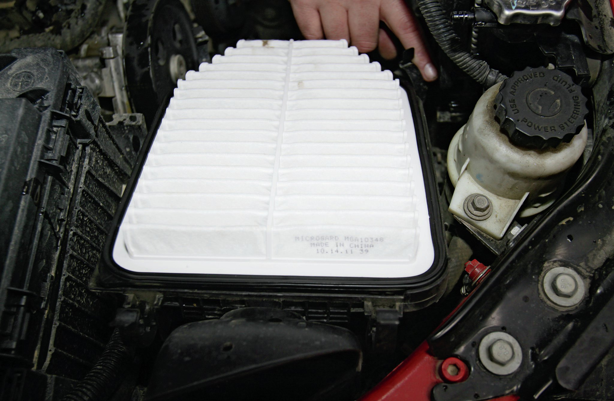 Since you're already up there, it would be a good idea to go ahead and change the air filter now. Undo the top cover by popping the four clips loose and replacing the filter with a new one, making sure it is well seated in the air box. One of the great mysteries of the world is the placement of the front-right clip. If you have large clumsy hands like me, a long screwdriver may help you to put that clip back in place.