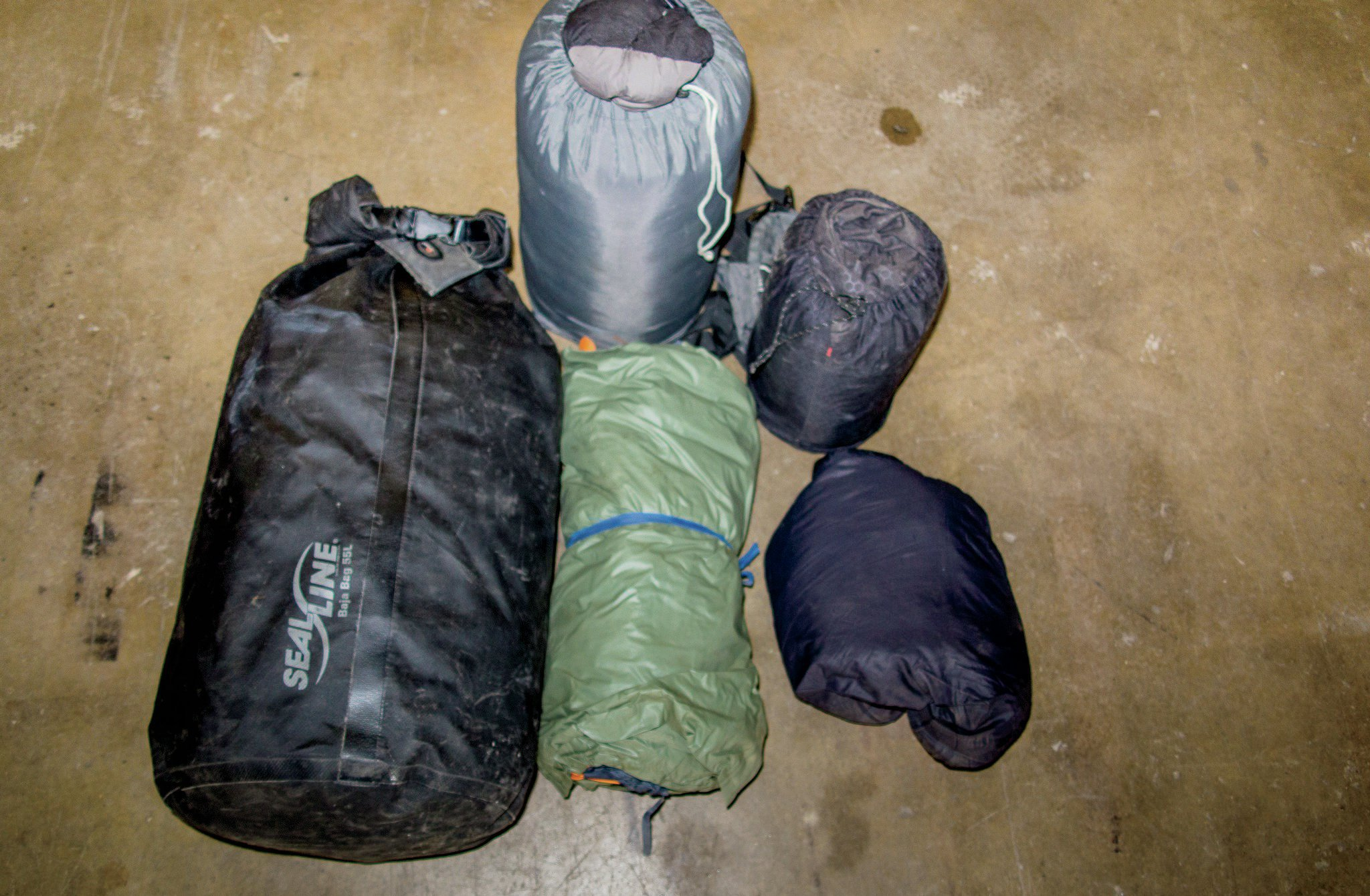 Dry bags make excellent storage for soft, light items such as sleeping gear. The bags are waterproof and dustproof and can be easily lashed to a roof rack. We keep our sleeping bag, tent, sleeping pad, and pillow all together in one bag. Note the poncho wrapped around the tent that doubles as a tarp.