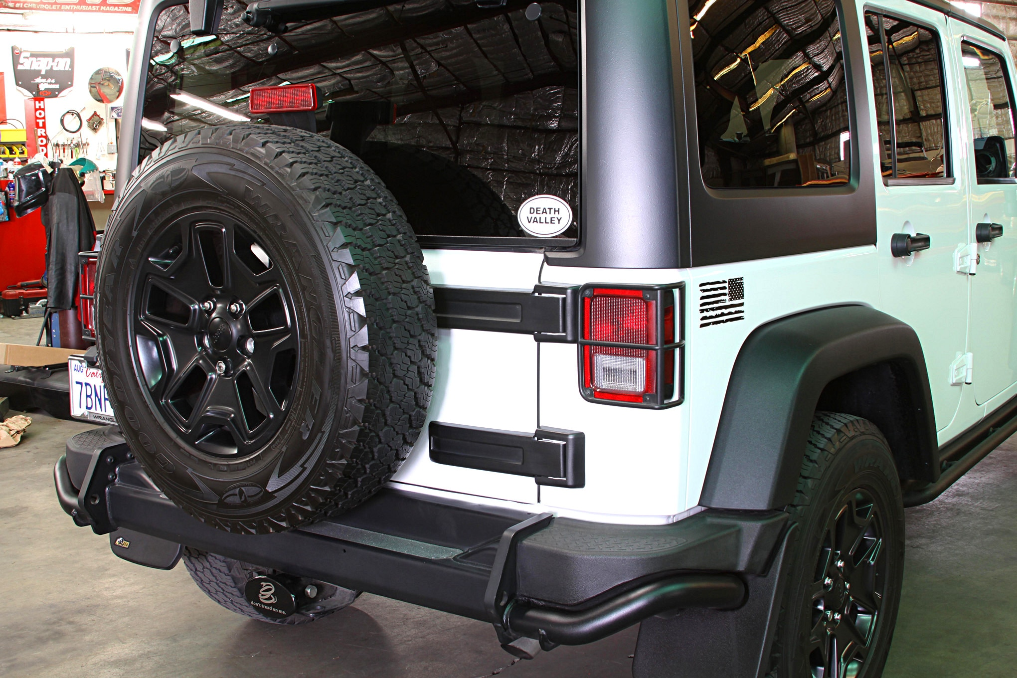 The back of our stock 2013 Jeep JK Unlimited Moab Edition Wrangler looked, well, stock. As with all factory Jeeps the spare hangs on the rear tailgate. This isn't a problem with stock rubber, but as you go bigger you also go heavier and that can place too much stress on the tailgate hinges. We decided to take advantage of the fact that our Moab came, from the factory, with AEV steel bumpers.