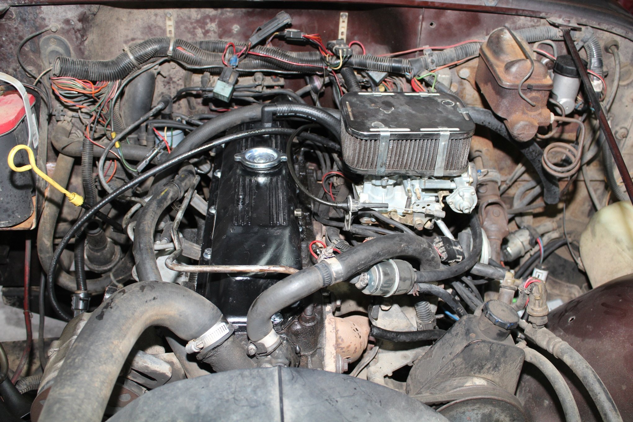 The later valve cover looks right at home on the earlier engine. Note that if your engine had a PCV valve, that hose needs to be connected to a specially ported nipple that will be present on the later valve cover. We managed to lose the nipple when we were cleaning up the valve cover, so we temporarily installed a plug until our next trip to the junkyard, at which time we grabbed a replacement.