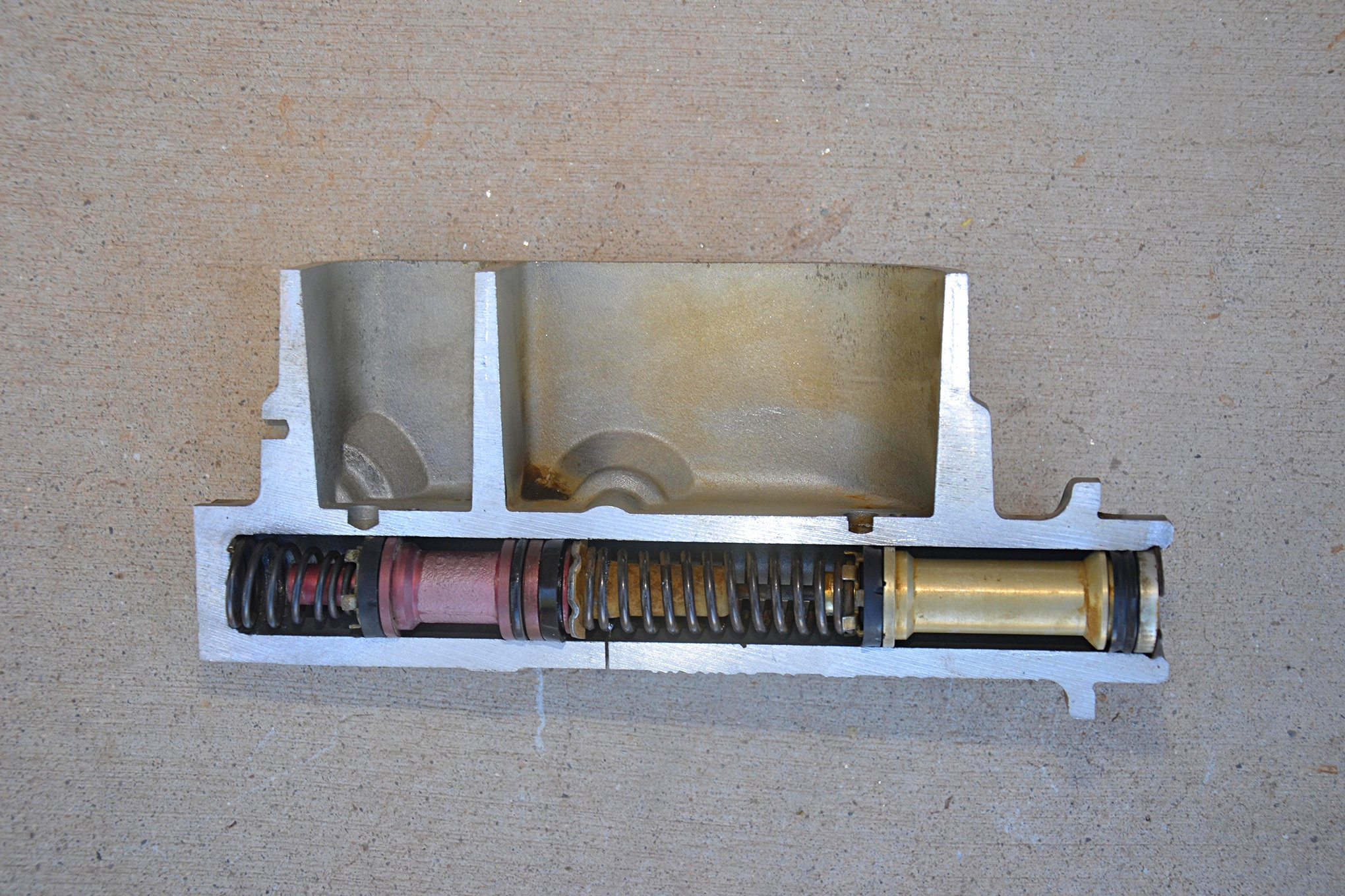 We cut through an old brake master cylinder to give you a look inside. You can see the two reservoirs for the two circuits, front and rear. Holes in the bottom of each reservoir allow fluid down into the system. Below, pistons slide past the fill holes and compress fluid as you press the brakes. Each piston has sweeper seals that match the inside diameter of the brake master cylinder and holes where front and rear brake lines lead to the proportioning valve or to the calipers and/or wheel cylinders.