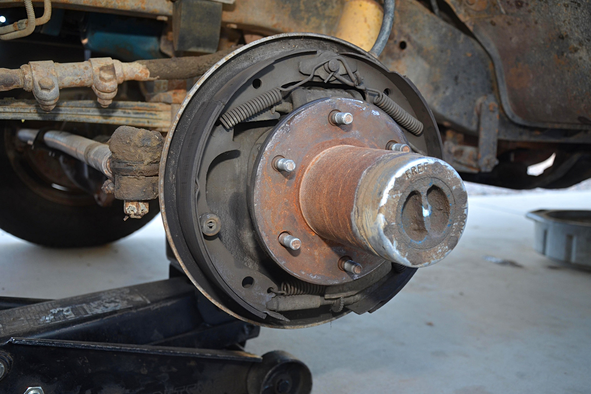 Various pins and springs allow the shoes (arrows) to move, allow parking brake systems to function, and servicing the brakes as they wear. At the bottom, an adjuster allows the brake pads to be moved out toward the drum as the pads and the drum wear. These adjusters are designed to self-tighten, but manual adjustment yields the best performance.