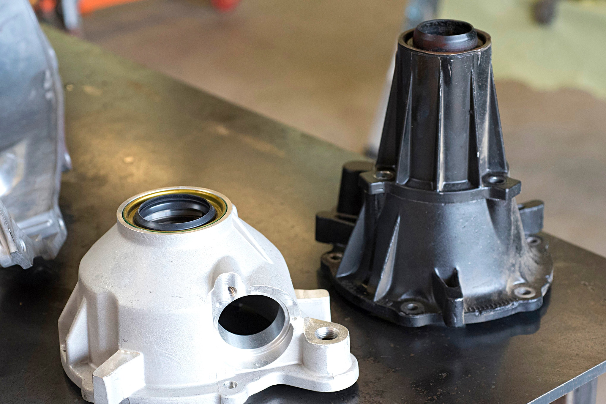 The slip-yoke eliminator kit uses of a much shorter output shaft housing (left) than OEM, which means a longer driveshaft can be used along with a 1310 U-joint. It also removes the oil seal leaking issue common to Jeeps.