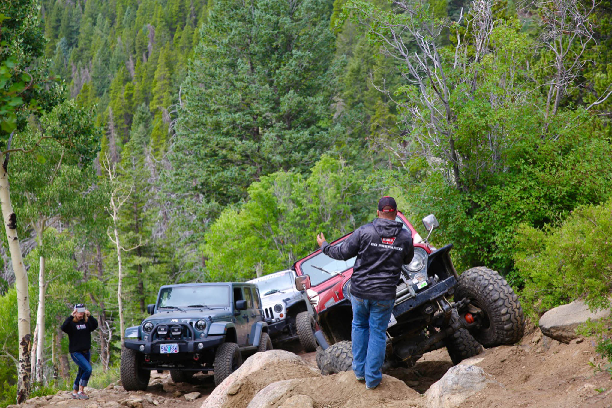 A member of the Warn crew spots for Dan Cavanaugh on a rocky section of Red Elephant Trail.