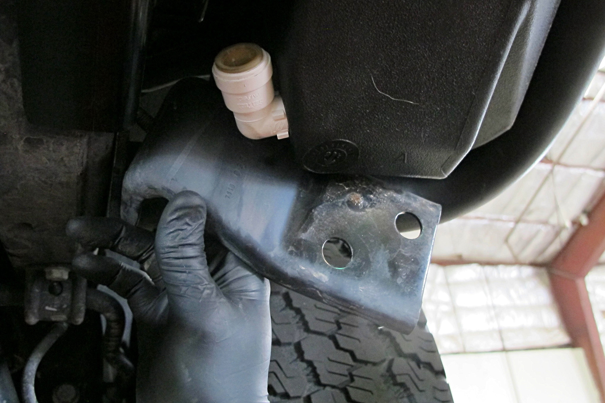 The water tanks, just like the blanks they replaced, were further secured using the existing brackets under the Jeep. We could then plumb the two tanks together and vent the passenger side tank per the AEV instructions.