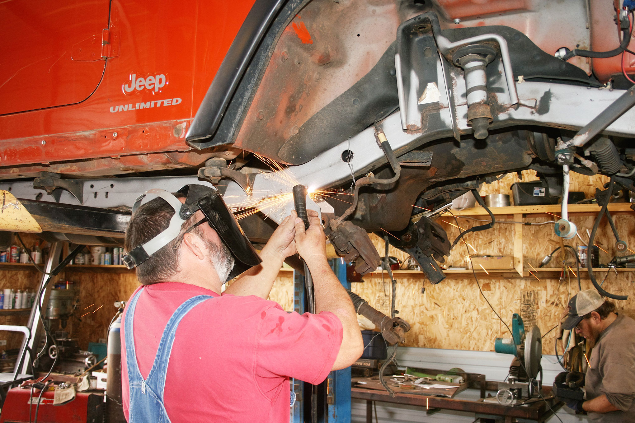 The OEM control arm mounts on the Jeep's frame rails must be removed before the TNT crossmembers can be mounted.