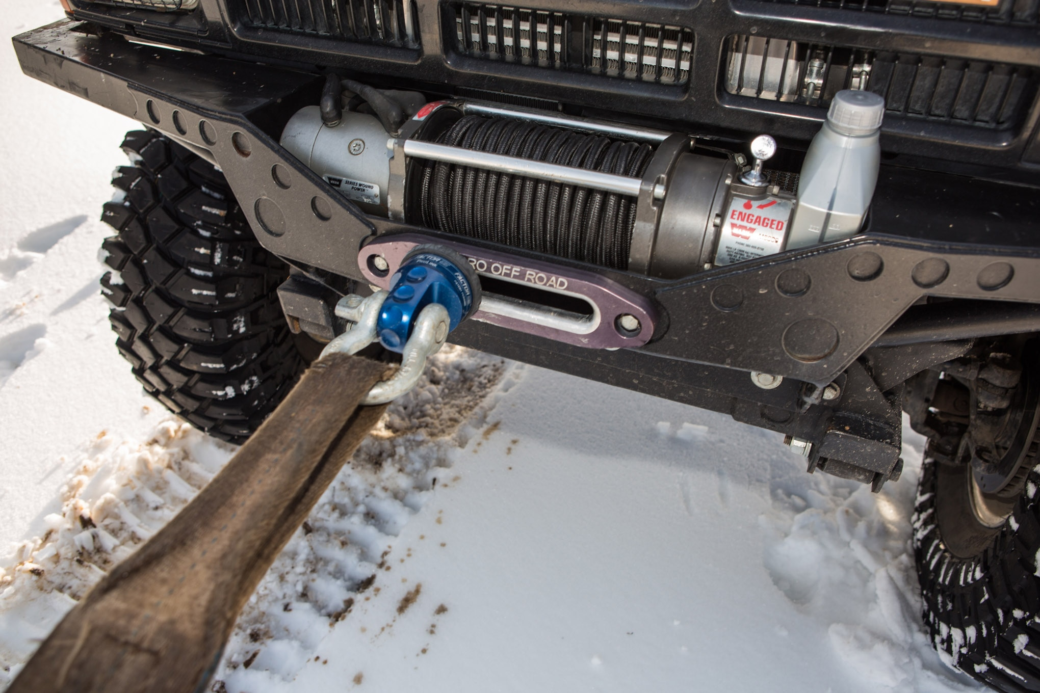 Never pull from your winch during a recovery. Only use sturdy recovery points attached to the frame. This advice is not specific to snow, and not doing it could damage the brake and other internal components in your winch.