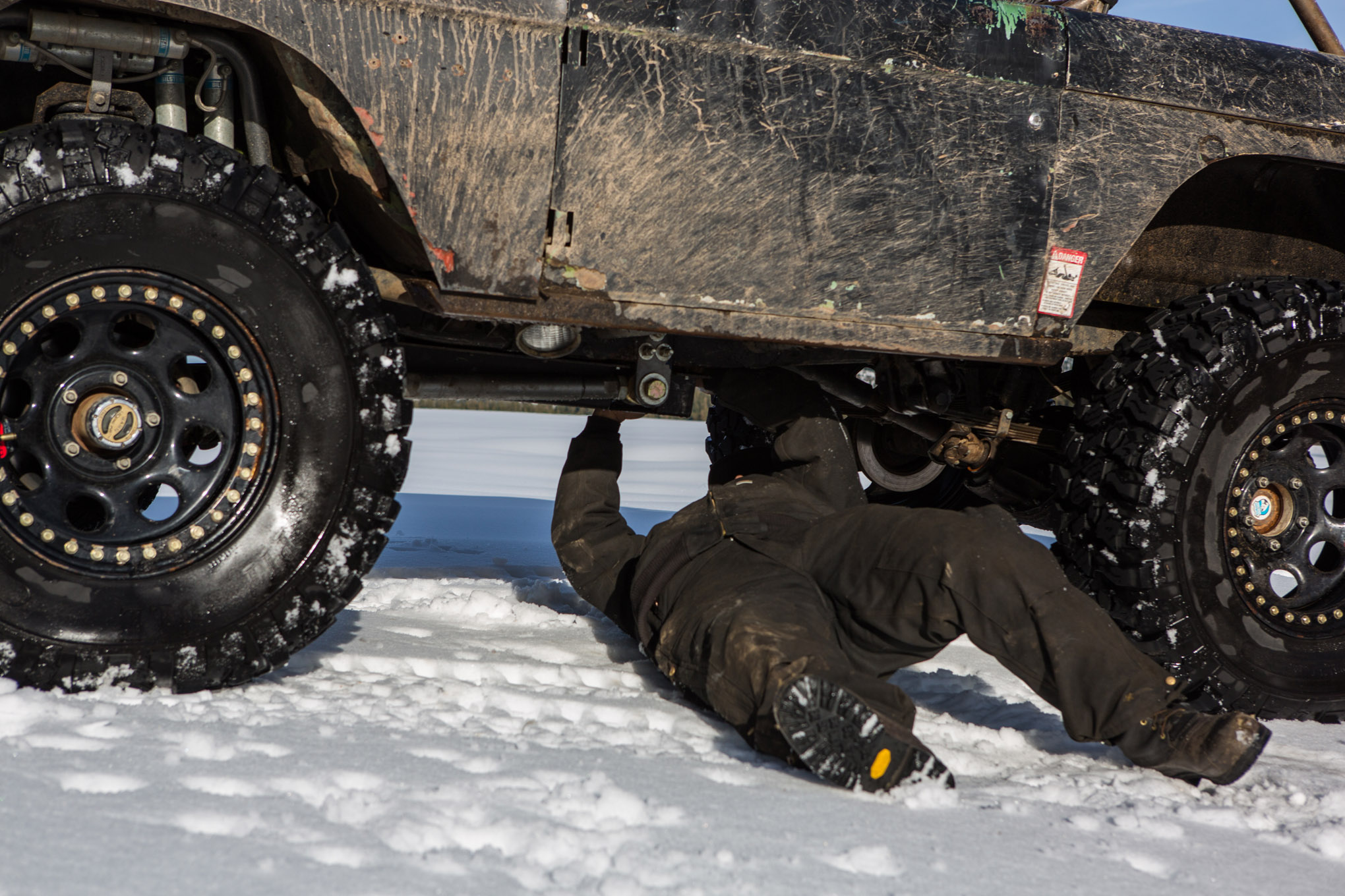 If you drive an open-topped rig, insulated Carhartts will be your new best friend. Grizzled snow-wheeling veteran Dave Perez says that he likes the bibs with an insulated jacket because they provide more options to tailor to the temperature than full coveralls do. He also recommends using a Utility Mat from Mac's Custom Tie Downs to lie down on in the snow.