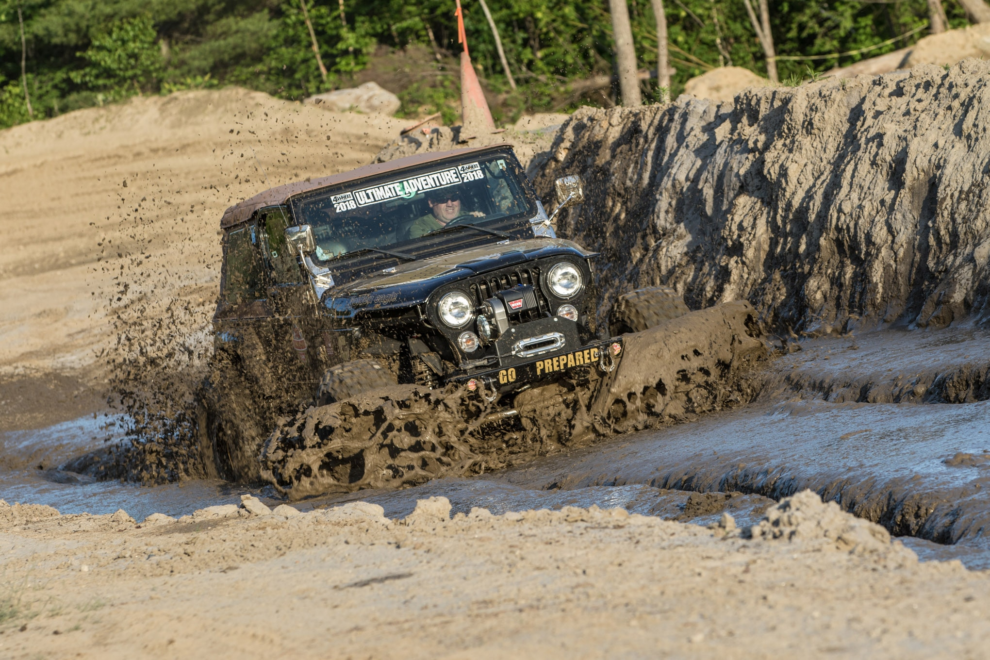 """Even with a stock 4.0L engine Corby Phillips wasn't scared to drive his Jeep through the mud pit. """"What's the worst that could happen? I have to use my winch?"""" the Warn rep joked. For the record, he made a clean run through the mud pit and made it through unassisted."""