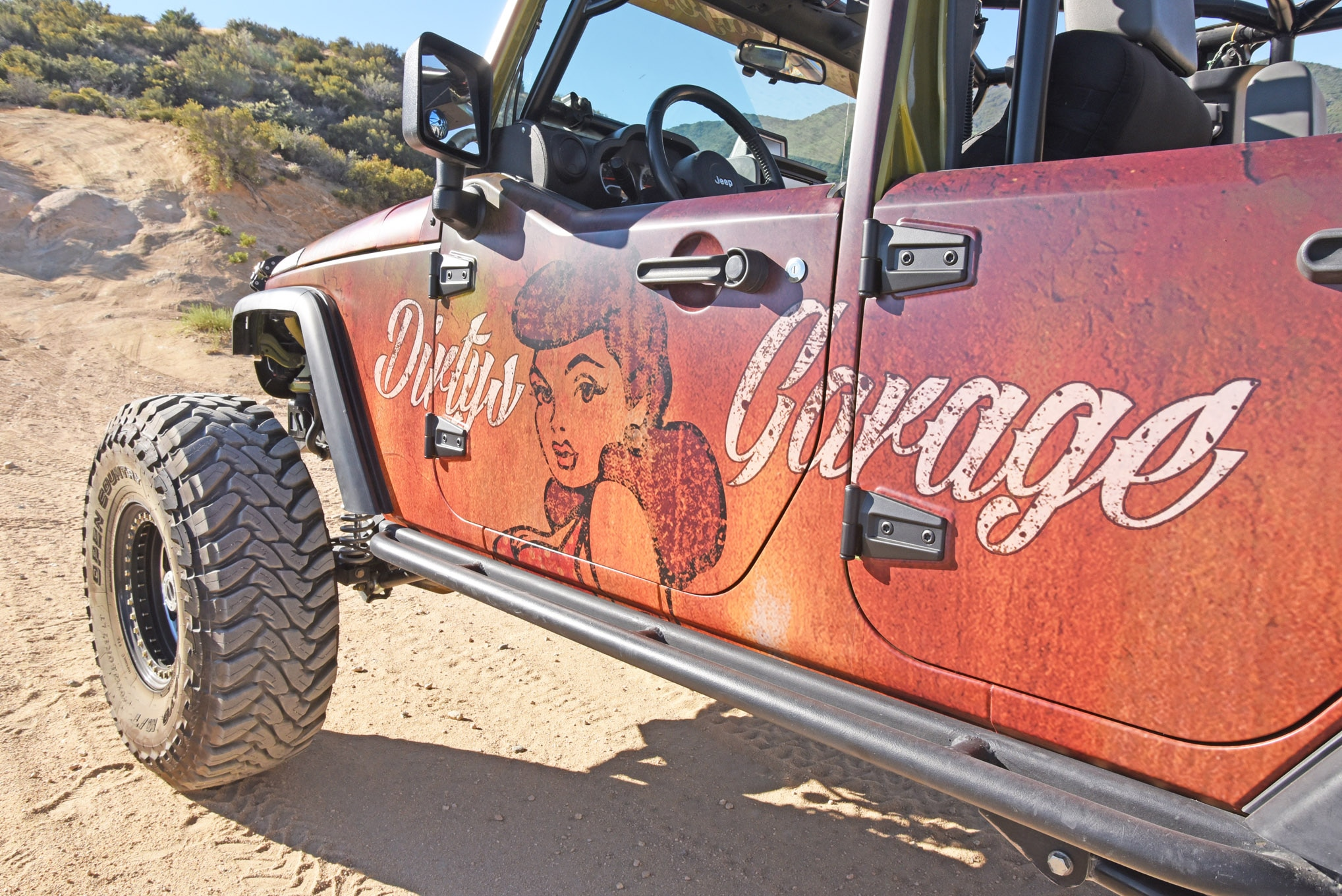 Scott not only uses his Jeep JKU as a daily driver, shop truck, and trail cruiser, it also serves as a wheelin' billboard for his custom 4x4 shop, Dirty's Garage. We like the patina and pinup styling he chose for the wrap.