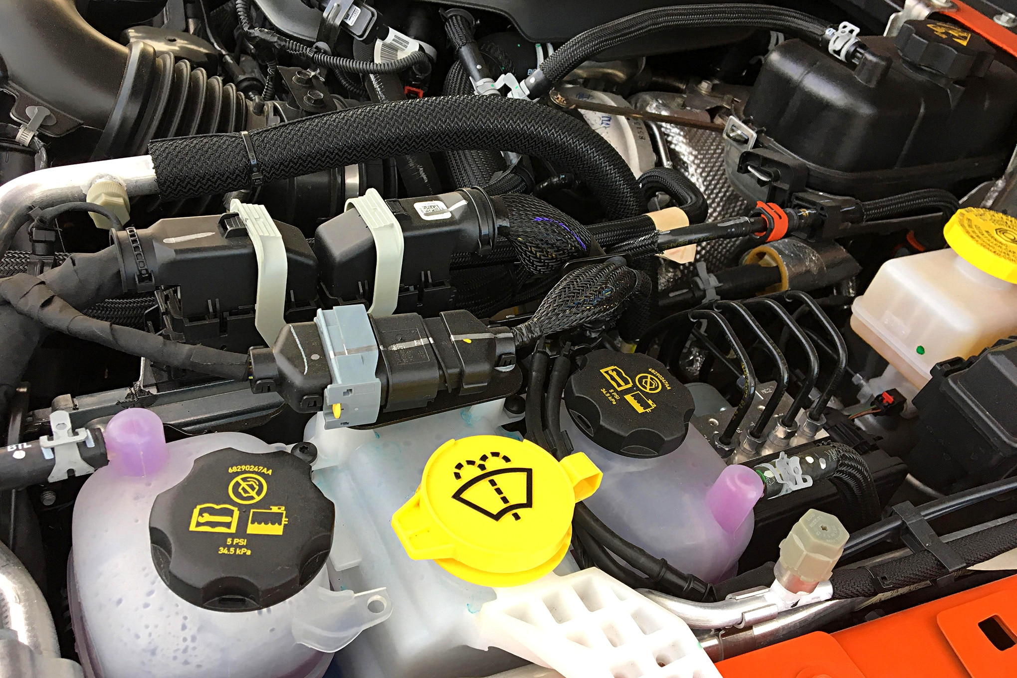 The JL's 2.0L turbo eTorque has three coolant reservoirs (hence three independent cooling systems): a motor-generator unit coolant reservoir in bottom left, turbo coolant reservoir in bottom center, and traditional engine coolant reservoir in top right. And not just any coolant—it must be Organic Additive Technology (OAT), conforming to FCA specifications.