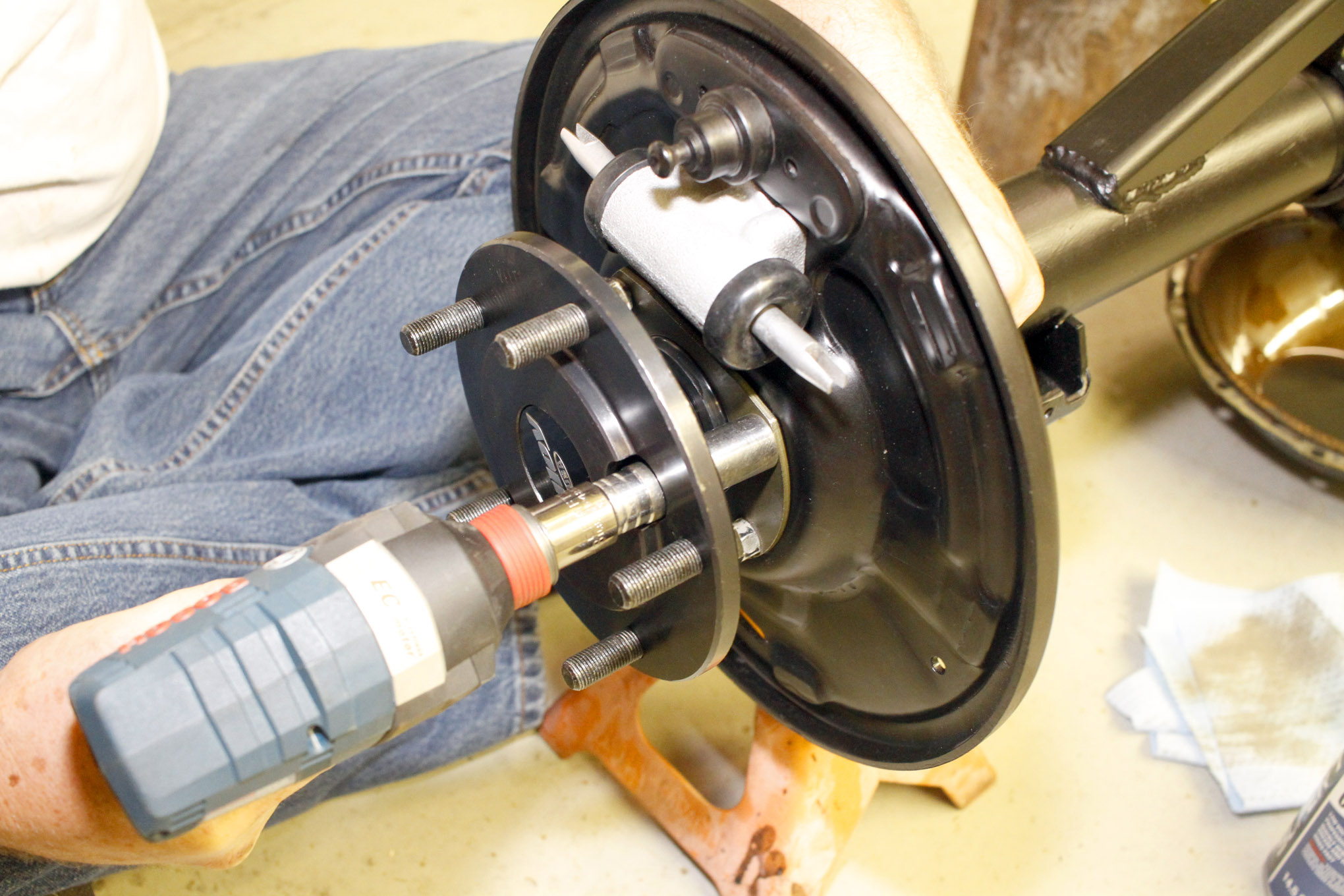 Each axle assembly was slipped into the axlehousing and then secured using four bolts per side. Tightening these bolts preloads the wheel bearing so that the outer race does not spin in the axletube bore. The Alloy USA wheel flanges have a hole in them to allow access to the bolt hardware.