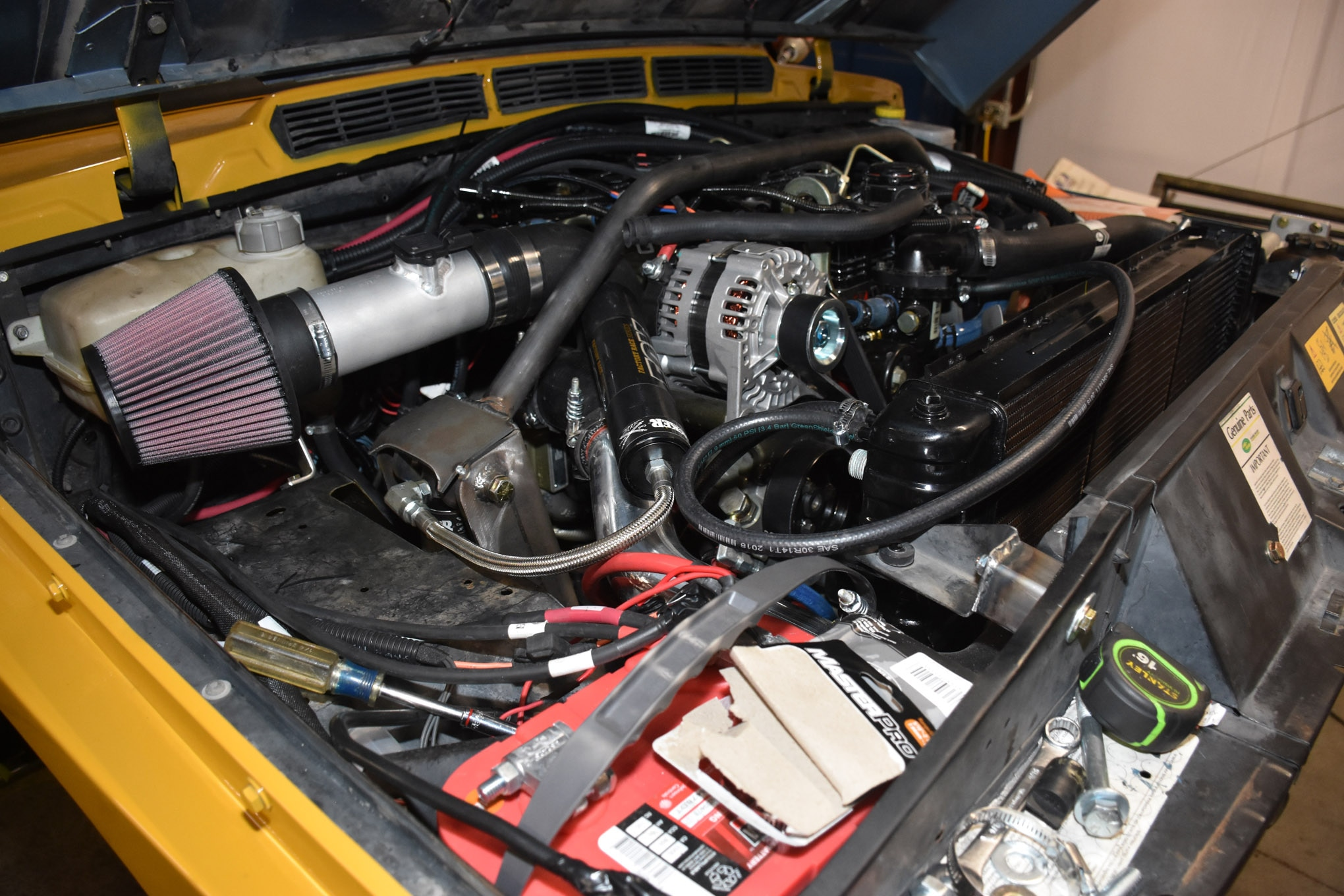"""As the """"Holy poop, we've got to get this thing done!"""" date for UA2018 rapidly approached, lots of things happened. To cool the R2.8, we fitted a factory-replacement Range Rover brass radiator from RockAuto.com. Then we pushed the radiator back as far as possible, leaving clearance for a 17-inch reverse-rotation steel Silver Race Fan from Flex-a-Lite and using an adapter to mount it to the R2.8's water pump from our friend Marc Terrien. To move the radiator, we drilled new holes for the radiator about 3 inches back from the factory position and built extensions for the upper radiator mounts. These radiators are held in place with two stems (like fingers) that point down to fit in rubber grommets that sink into the front crossmember. Up top are some fingers (pointing up) that are grabbed by brackets isolating the radiator with some rubber grommets. Pretty ingenious, Brits!"""