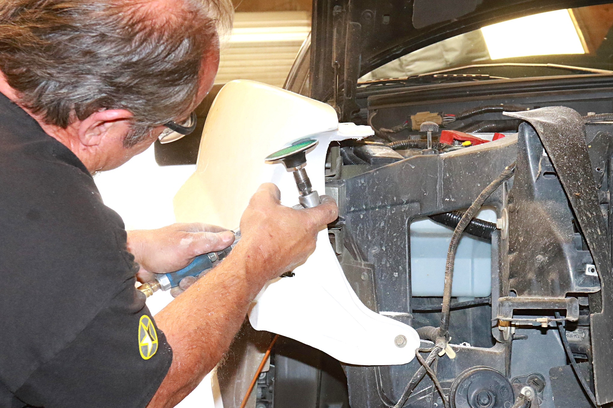 With the fenders bolted on, Louis works the headlight pocket to get it to perfect.