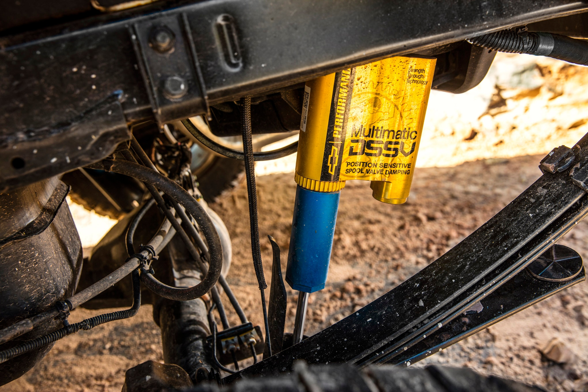 The Multimatic DSSV dampers on the Colorado ZR2 are unlike anything seen before. These shocks have a main body where the shaft rides and the extreme compression spool valve is housed; a middle chamber that houses the on-road compression and rebound spool valves; and a third chamber that acts as a fluid reservoir and separates the nitrogen charge from the hydraulic fluid. As the piston moves through the on-road zone, oil is forced into the spool valves housed in the middle chamber through special orifices in the body. When the shock is compressed outside of the normal zone, the third spool valve mounted on the shaft takes over damping duties. And during extreme rebound situations, such as having the wheels off of the ground, a special rebound valve at the base of the main body controls the motion. All of this combines to create a damper that works exceedingly well on the highway and in the dirt, with almost no compromise.