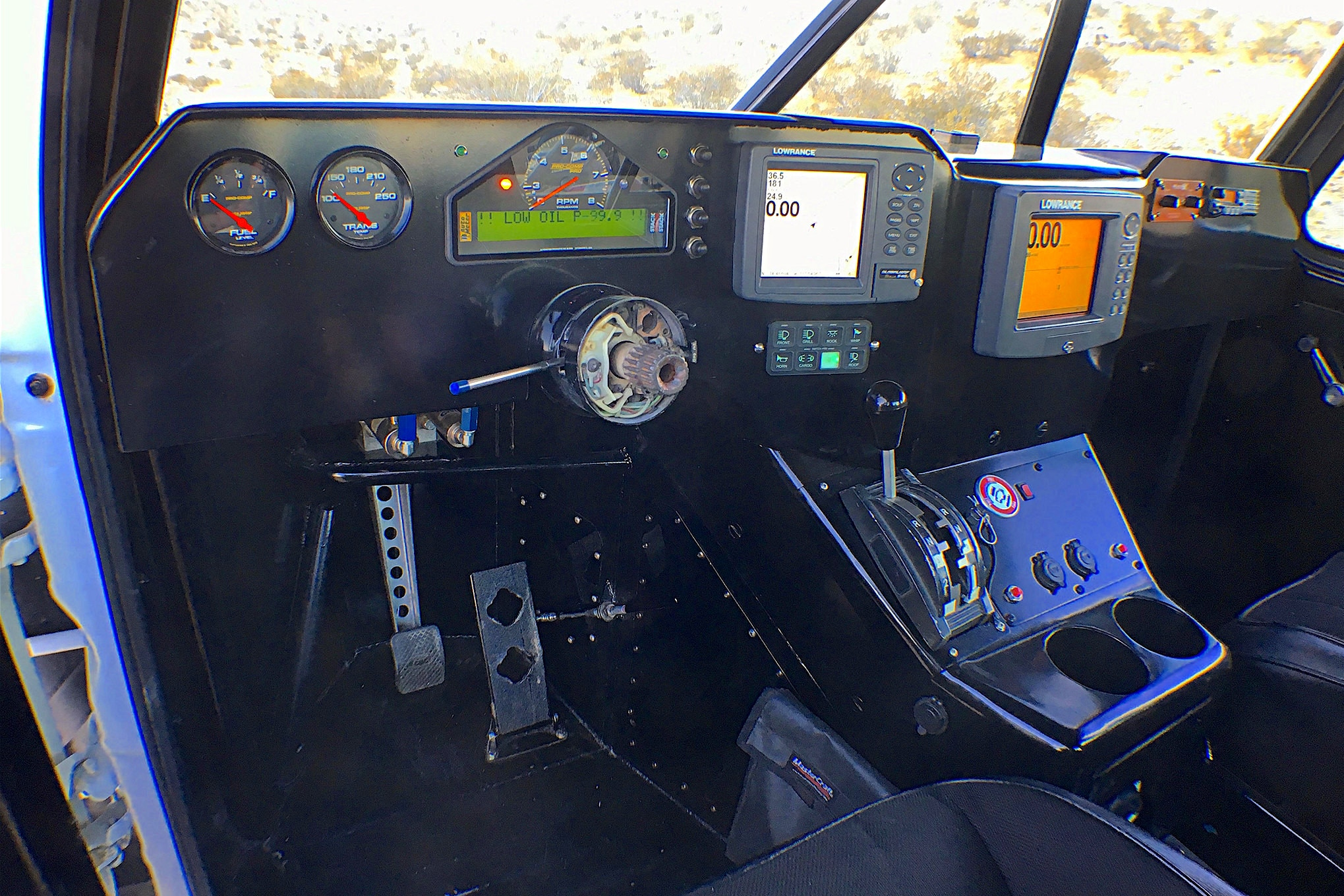 An Auto Meter dash pack, Lowrance GPS units, and an Icom radio/Racer X intercom is situated in the handmade dash.