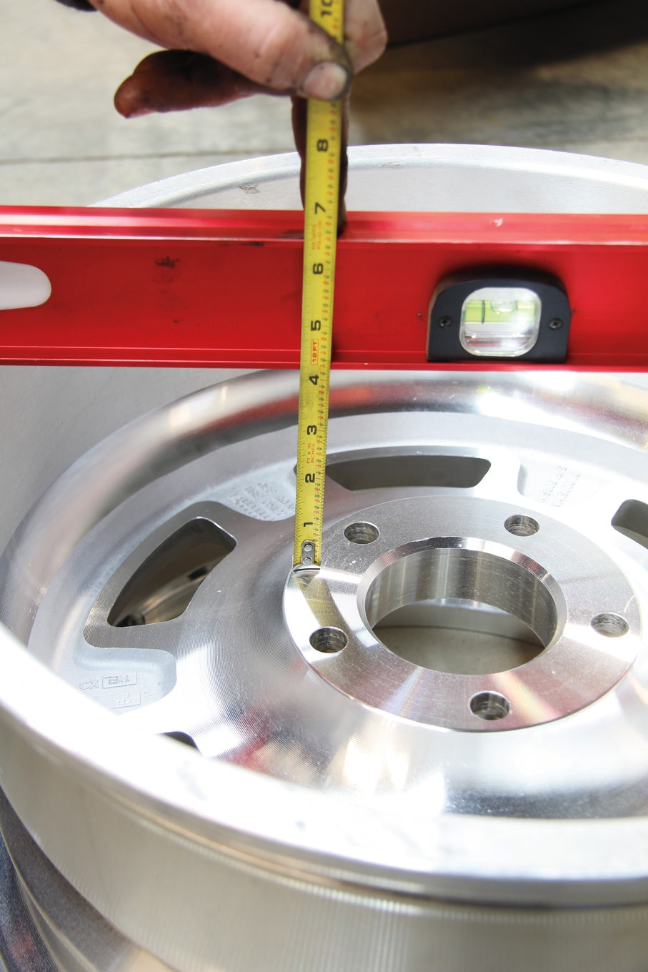 Measuring backspacing is pretty easy. Place a straightedge across the outside surface of the inboard rim, and use a ruler to measure the distance from the hub mating surface on the back of the wheel (shown here) to your straightedge.