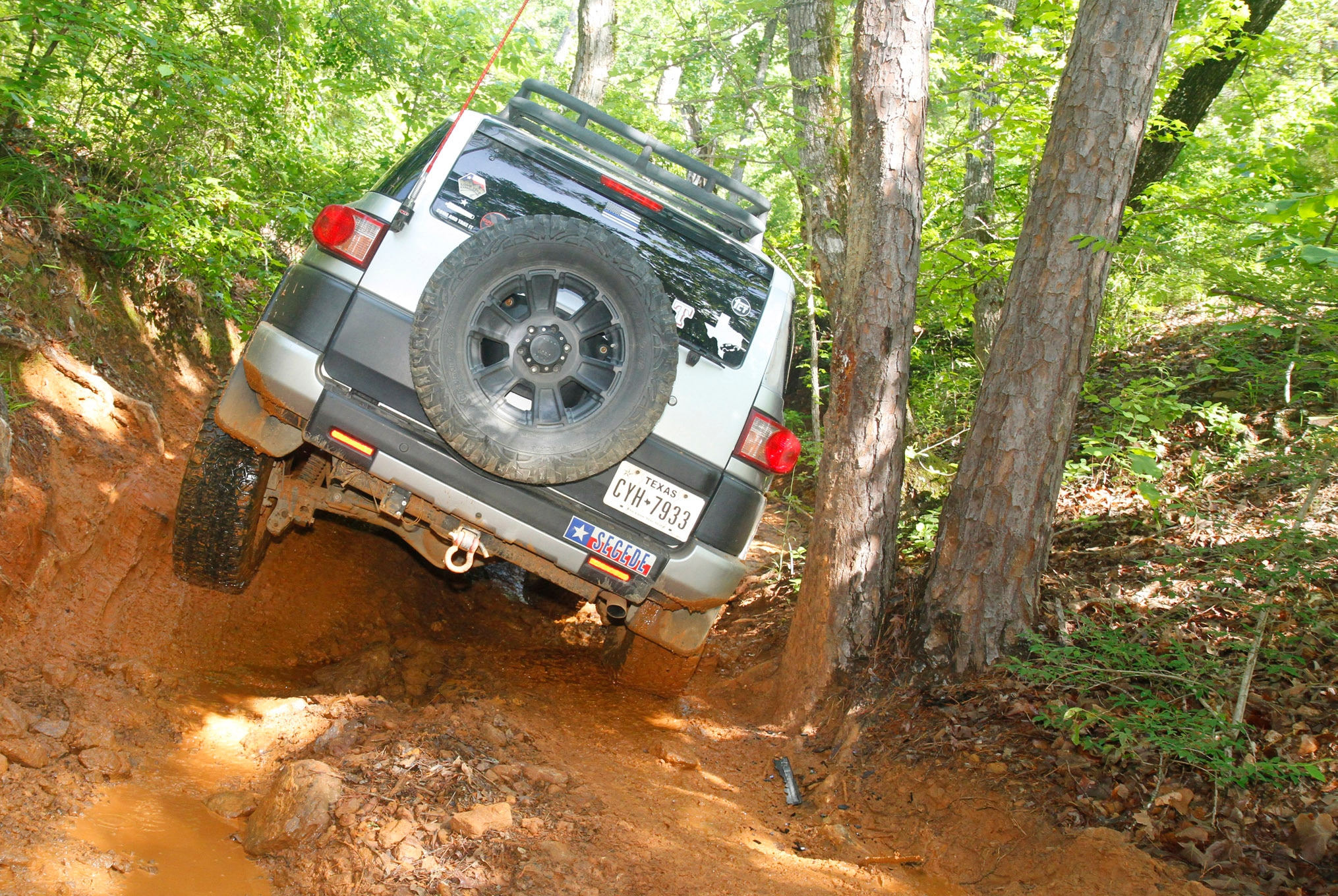 This tight, off-camber squeeze on Spider Ravine caught a few drivers by surprise, tipping most rigs towards a tree. This FJ Cruiser driver slipped through rather quickly, but it cost him a few body dents and broken window glass.