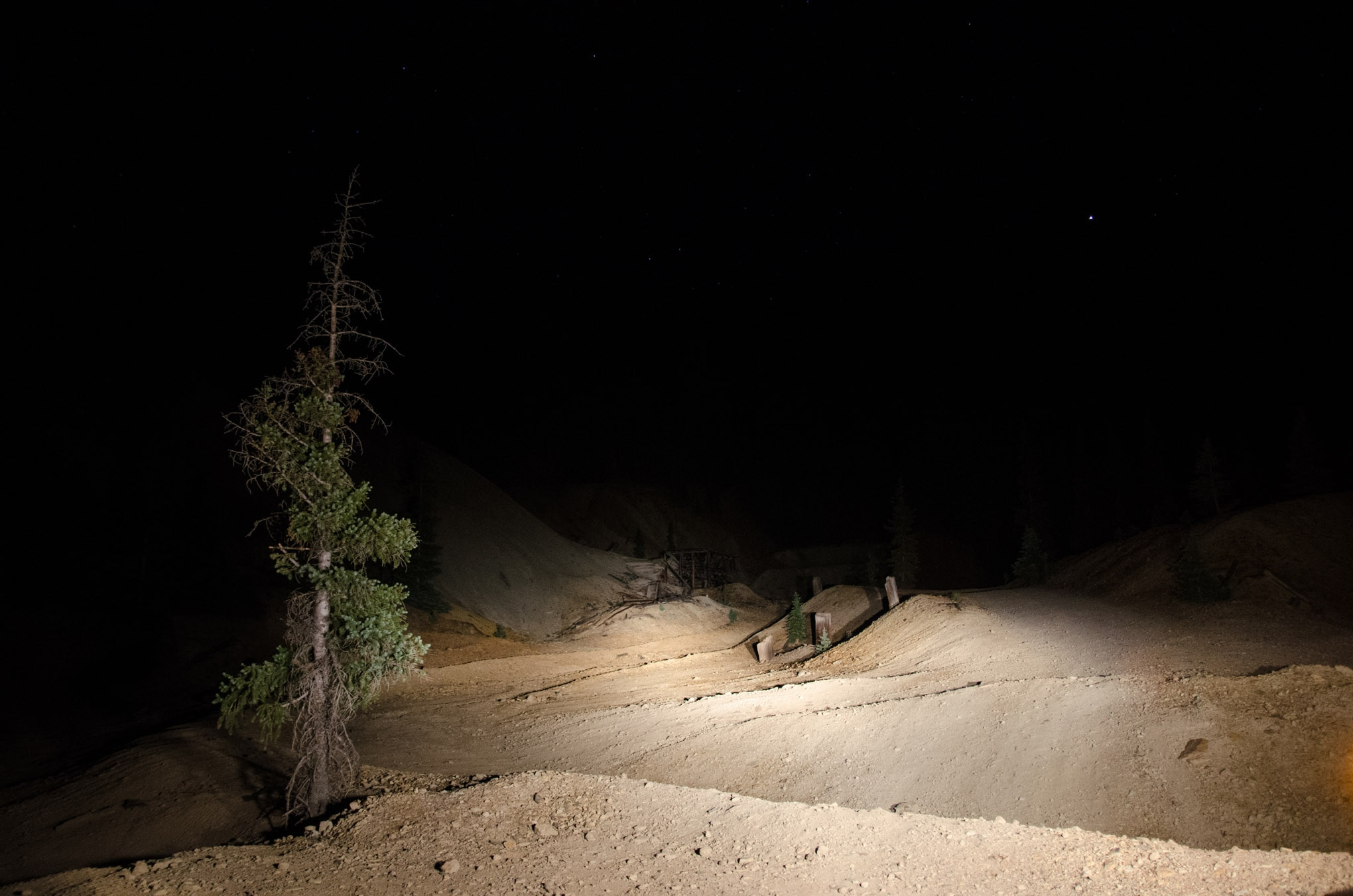 These two photos show the difference in visibility between using just the high-beam headlights and the ADV Light Cannons. A tripod was used in the same position along with the same camera settings for both images. The ADV lights clearly highlighted the collapsed mine ore hopper that was barely visible with our headlights as well as illuminating the hillsides and more of the trail ahead.