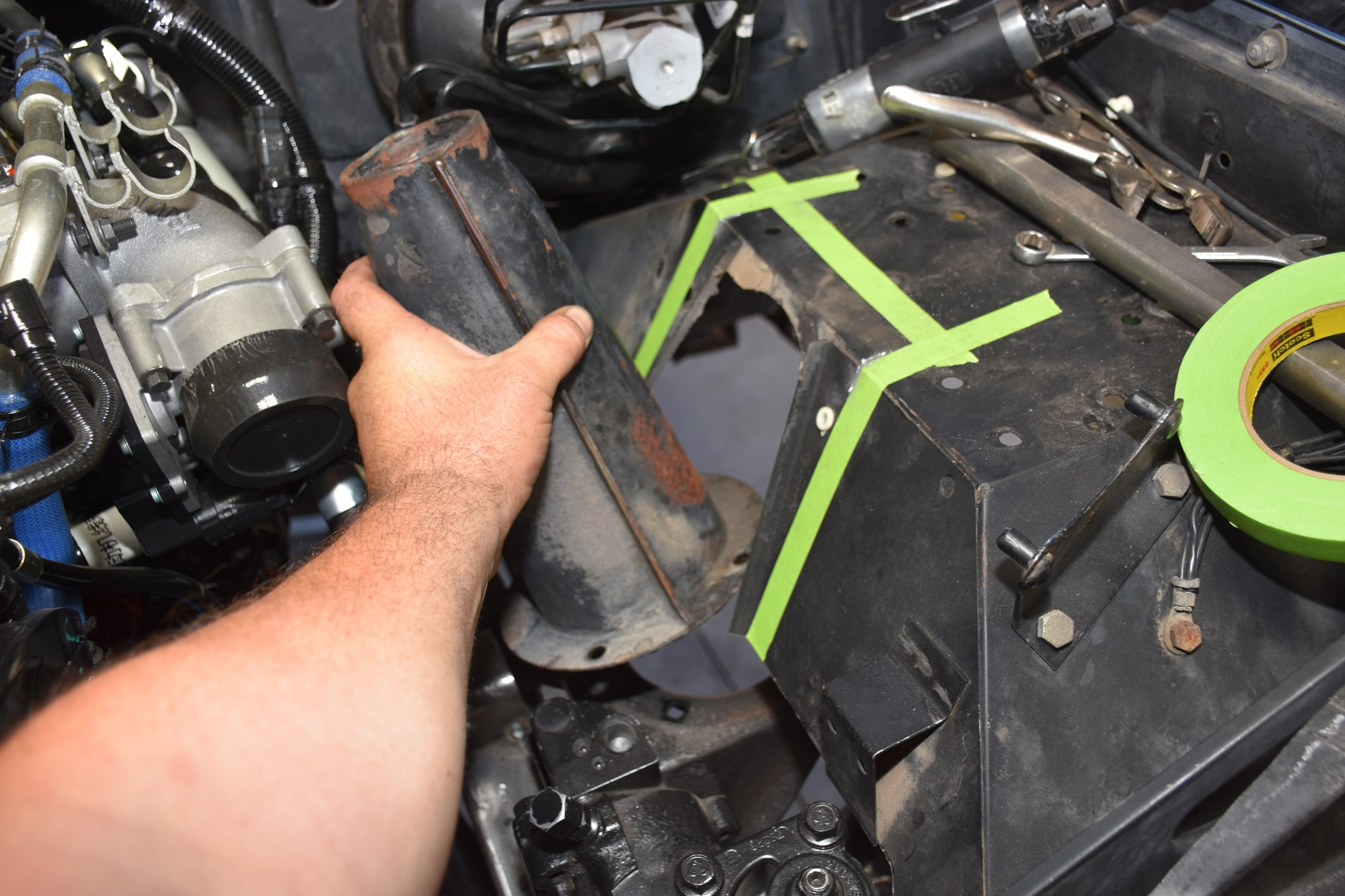 With the right-hand-drive JK steering box from West Texas Offroad roughly in place and connected to the steering column with Borgeson steering U-joints and a collapsible shaft, we started fabbing up shock mounts for the front of the Derange Rover. We mocked up shock towers for Skyjacker LeDuc series coilovers using cardboard. First step was to remove the factory shock mount and part of the coil mount.