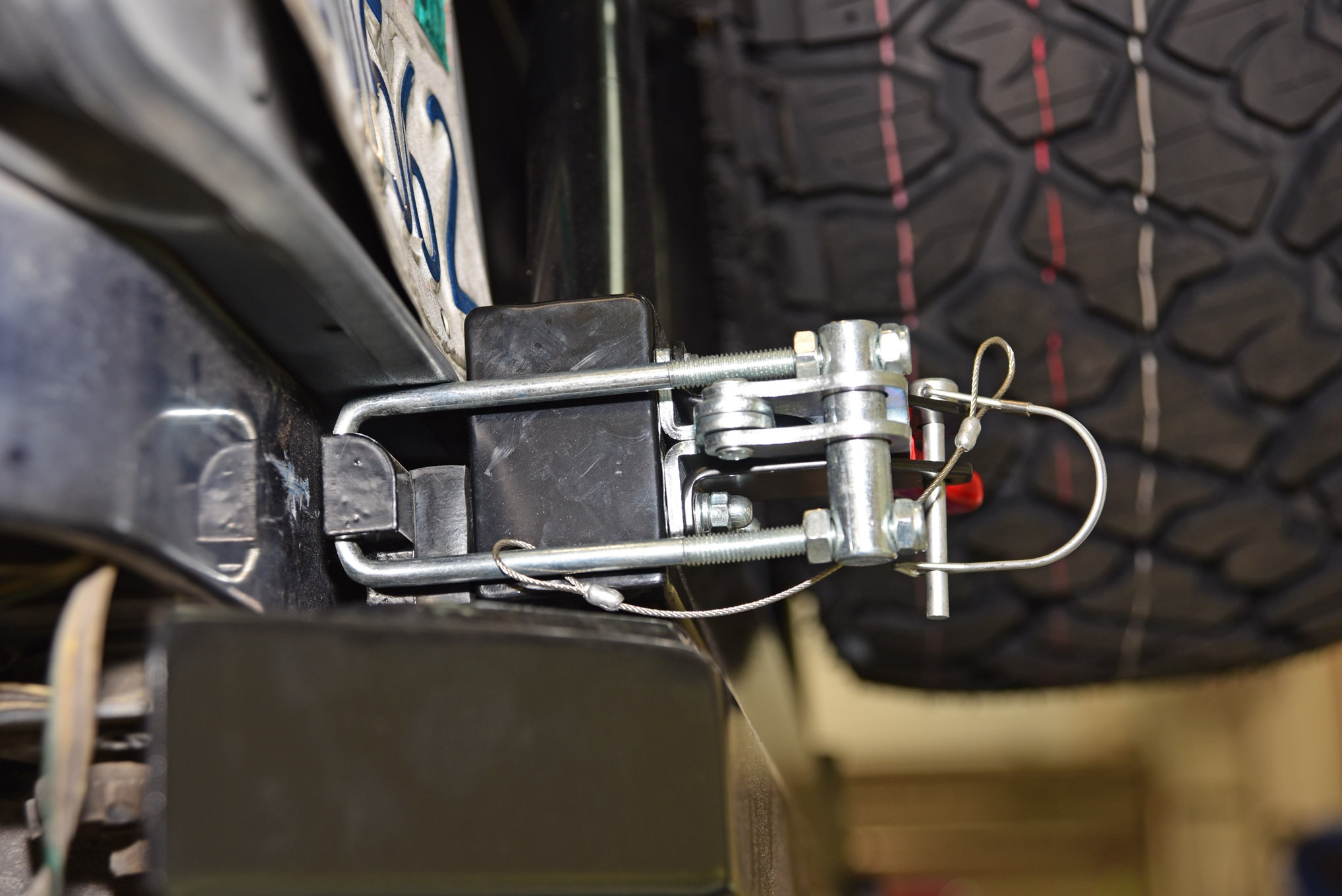 A kit-supplied latch had been assembled and installed (including the rubber stop block on the bumper) onto the swing-out carrier. When properly installed and adjusted, the latch assembly will tightly hold the tire carrier closed to the rear Rampage Recovery bumper.