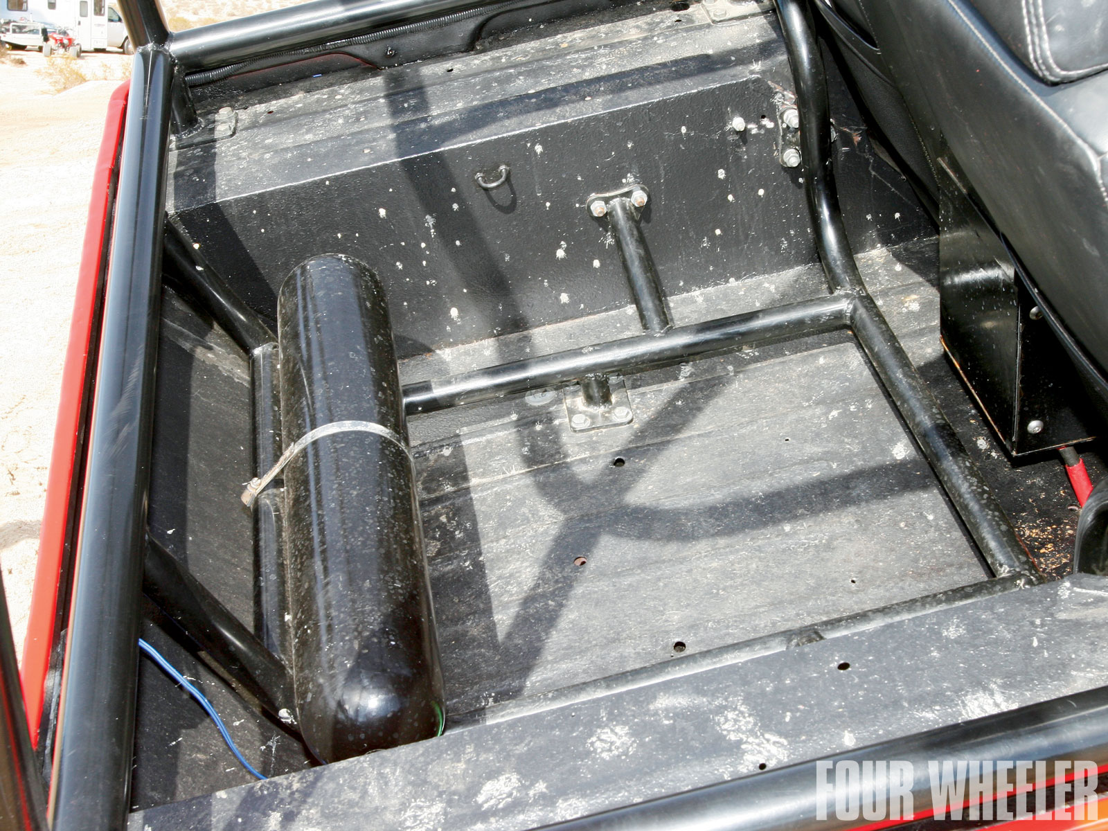 "The cargo area has plenty of room for gear, even with the full rollcage. Speaking of the rollcage, it's made from 2-inch-diameter, 0.095-inch-wall tubing. Hilton made the 'cage to his specs. ""I was tired of hitting my head on stock cages, so I built mine a bit higher to fit me. The 'cage is connected to the frame in six places, but it is bolted through the tub to the frame so it can be removed from the tub with no cutting,"" Hilton says. When we photographed the rig, the cargo area was mostly empty with the exception of the 2 1/2-gallon Peterbilt auxiliary air tank."