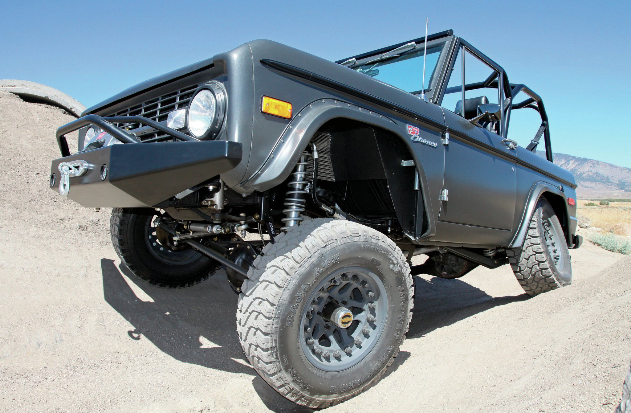 The custom-built suspension is designed to work above and beyond the off-the-shelf kits commonly sold for the '66-77 Early Bronco. The trickery isn't fully apparent at a casual glance. You've got to crawl underneath to really understand what's going on.