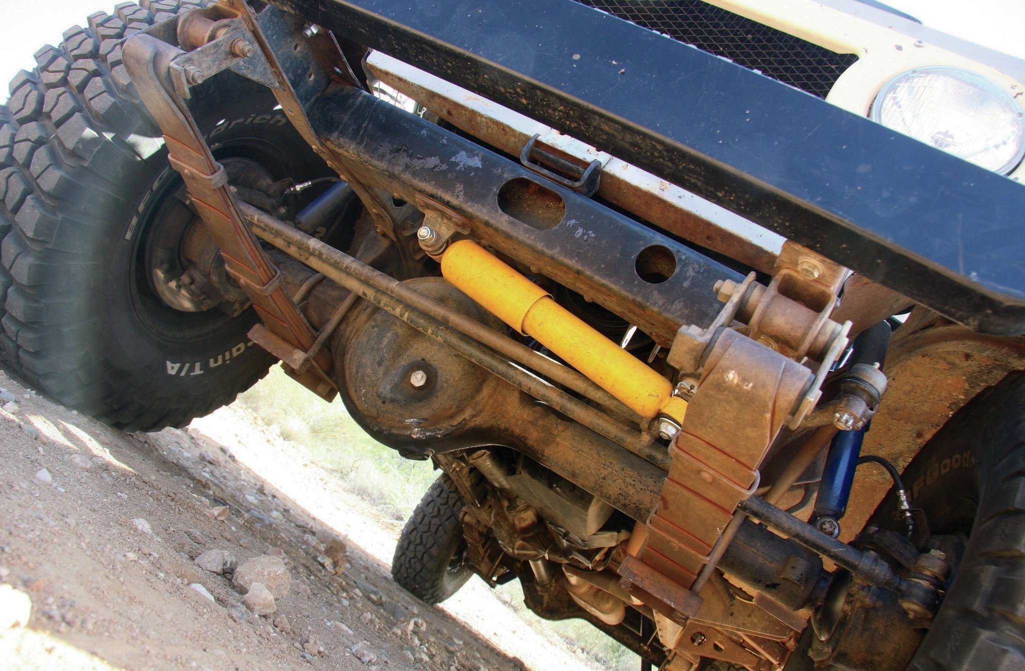 Under the front are the original factory leaf springs supplemented with a fresh pair of NAPA shocks and steering stabilizer. The aged springs are now supported by a '72 FJ55 axlehousing. The axle was rebuilt and the outer components replaced with stouter mini-truck parts, including the manual locking hubs. Larger 4Runner brake calipers and vented rotors were installed to increase braking power. Gears are 4.10s for a good mix of off-road and street performance.