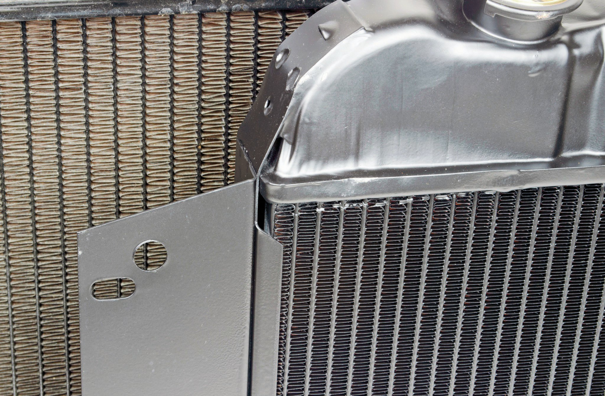 "You'll hear ""high efficiency"" used a lot to describe a radiator. This has to do with the tube and fin layout. This U.S. Radiator (in front) features the company's high-efficiency core, which uses 1⁄2-inch tubes on 3⁄8-inch centers, compared to most old brass and copper radiators which have the tubes mounts on 9⁄16-inch centers. This means more tubes and more contact with cooling fins for better heat transfer. U.S. Radiator offers various core designs to match what you need in a specific application."