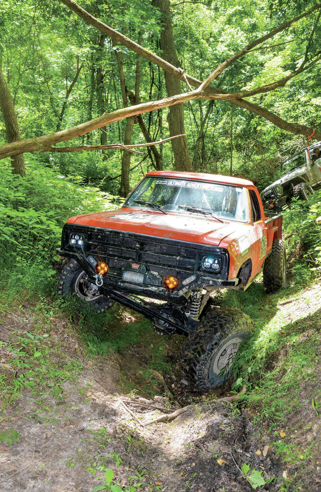 The next obstacle on the Atlas Trail, called Bad Dog, began with a twisty muddy wash. The Tug-Truck threads the needle below some fallen logs while getting seriously twisted up. It's big. It's orange. It's the Tug-Truck!