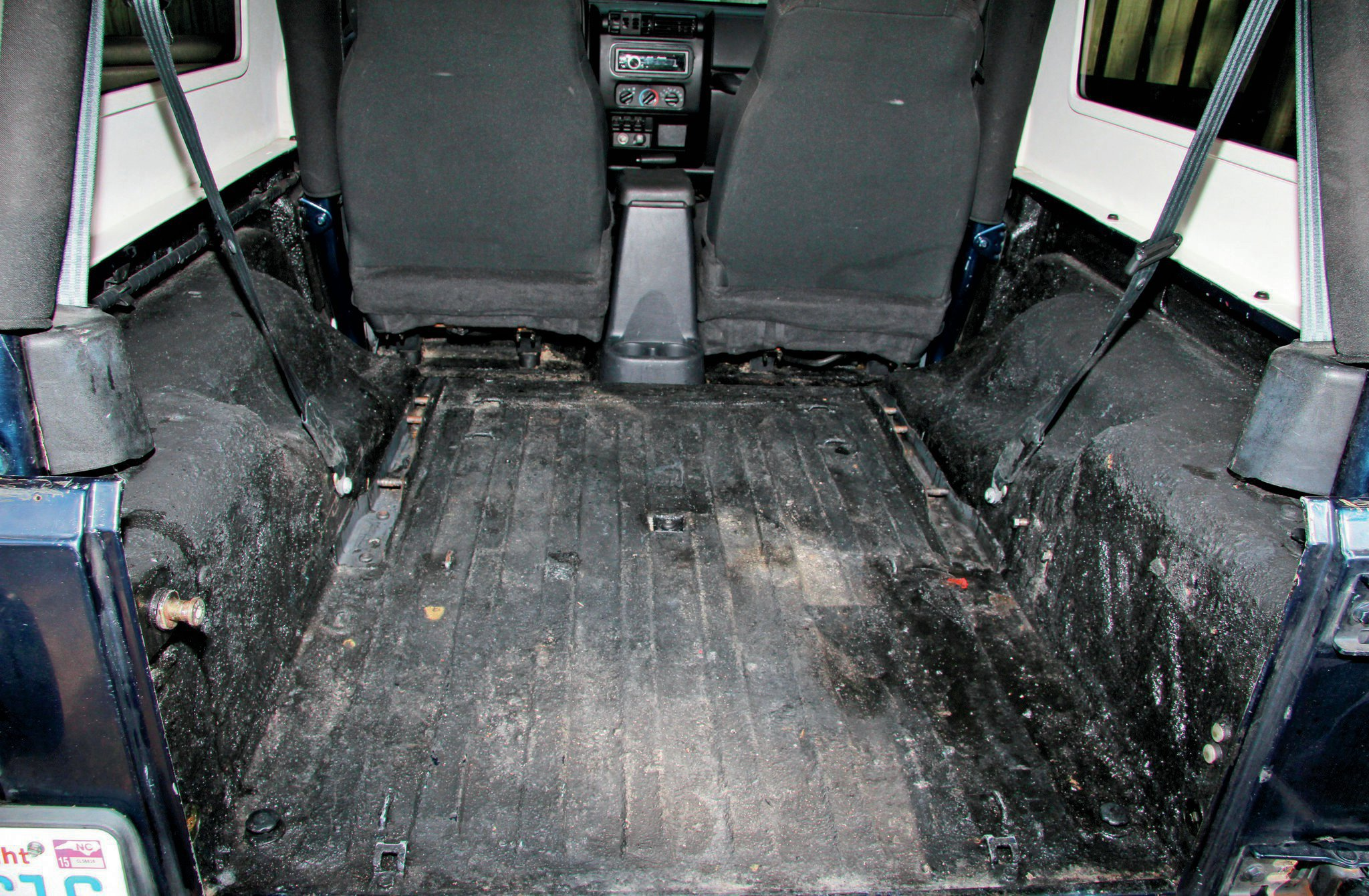 Our '04 Unlimited was fit with a DIY bed liner, which had seen better days. Using some Simple Green and a brush, we scrubbed and vacuumed the inside of the Jeep to prep for the new BedRug.