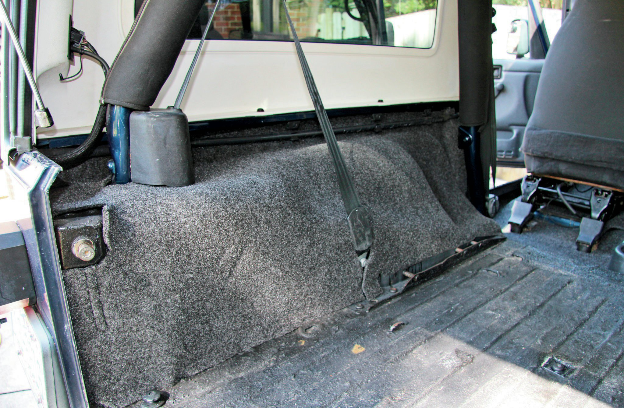 We got to guinea-pig BedRug's new Unlimited LJ kit and were stoked that it fit without any issues. The sides of the rug install first and simply slide behind the seatbelts. All necessary notches and openings were already in place.