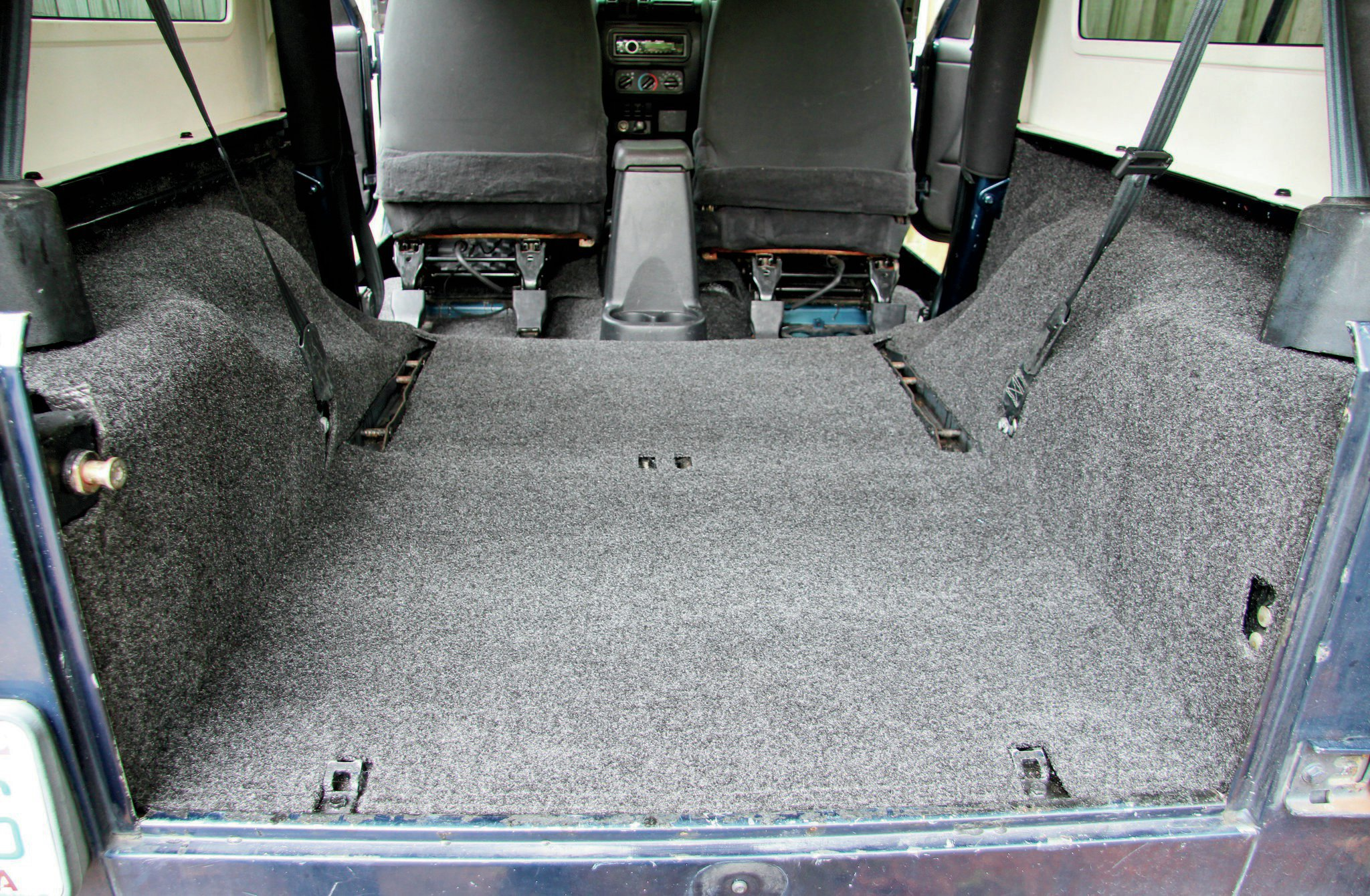 BedRug knows that many Wrangler owners choose to remove their rear seats, so they offer the kits with or without access openings for the rear seat. We move our rear seat in and out frequently since we have a kiddo in the mix. This means we prefer to keep the stock seat brackets in. We opted to have the seat belt openings as well as the seat brackets cutout from BedRug. The fit was spot-on.