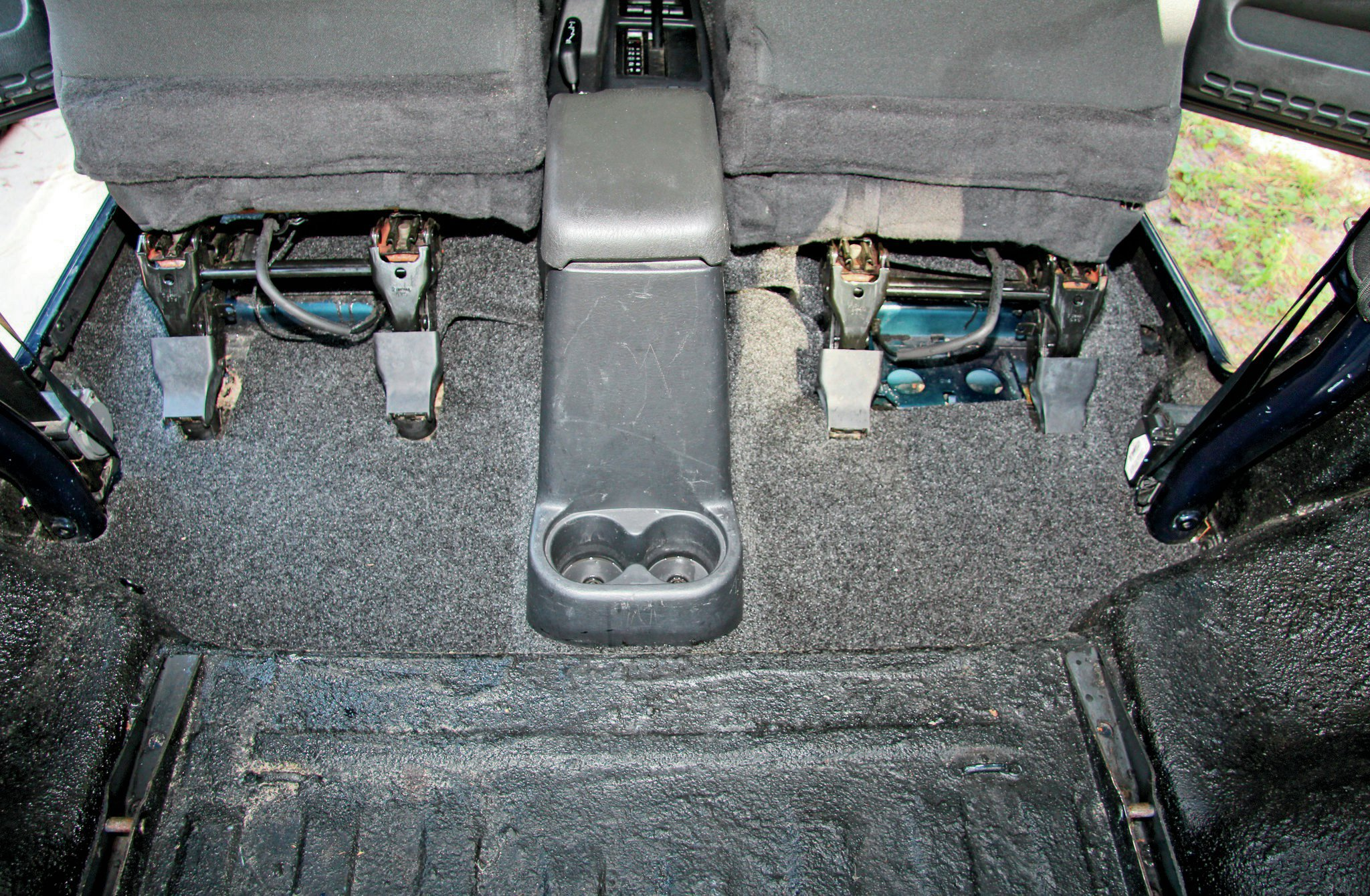 To secure the rear portion of the BedRug behind the front seats, you will need to remove the two bolts that attach the rear portion of the center console. Doing so will allow you to more easily fit the BedRug in place.