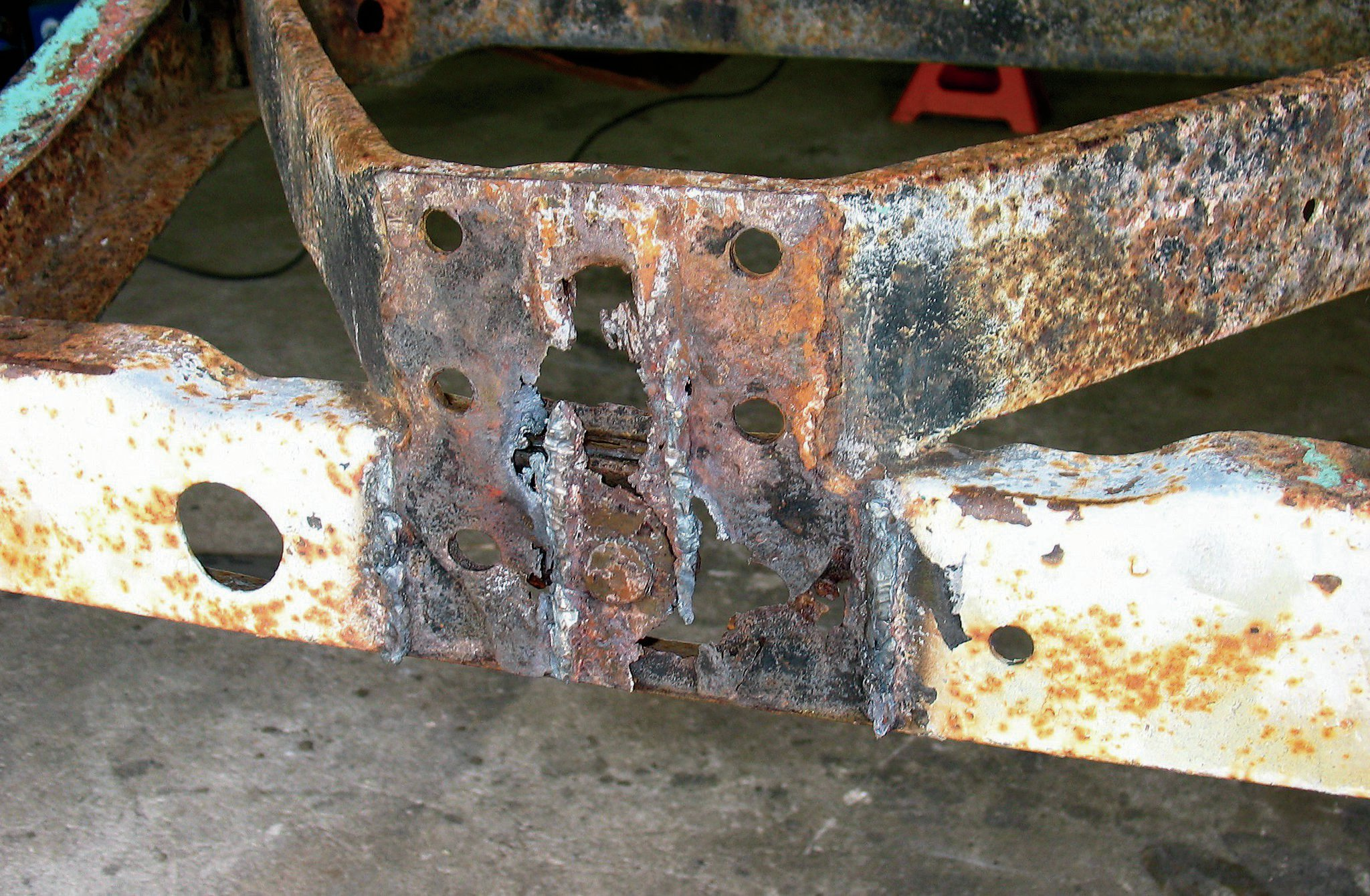 After removing the welded- and bolted-on tow hitch from the rear bumper area of our frame, we were left with this rusty mess. We used a 41⁄2-inch angle grinder to clean it up.