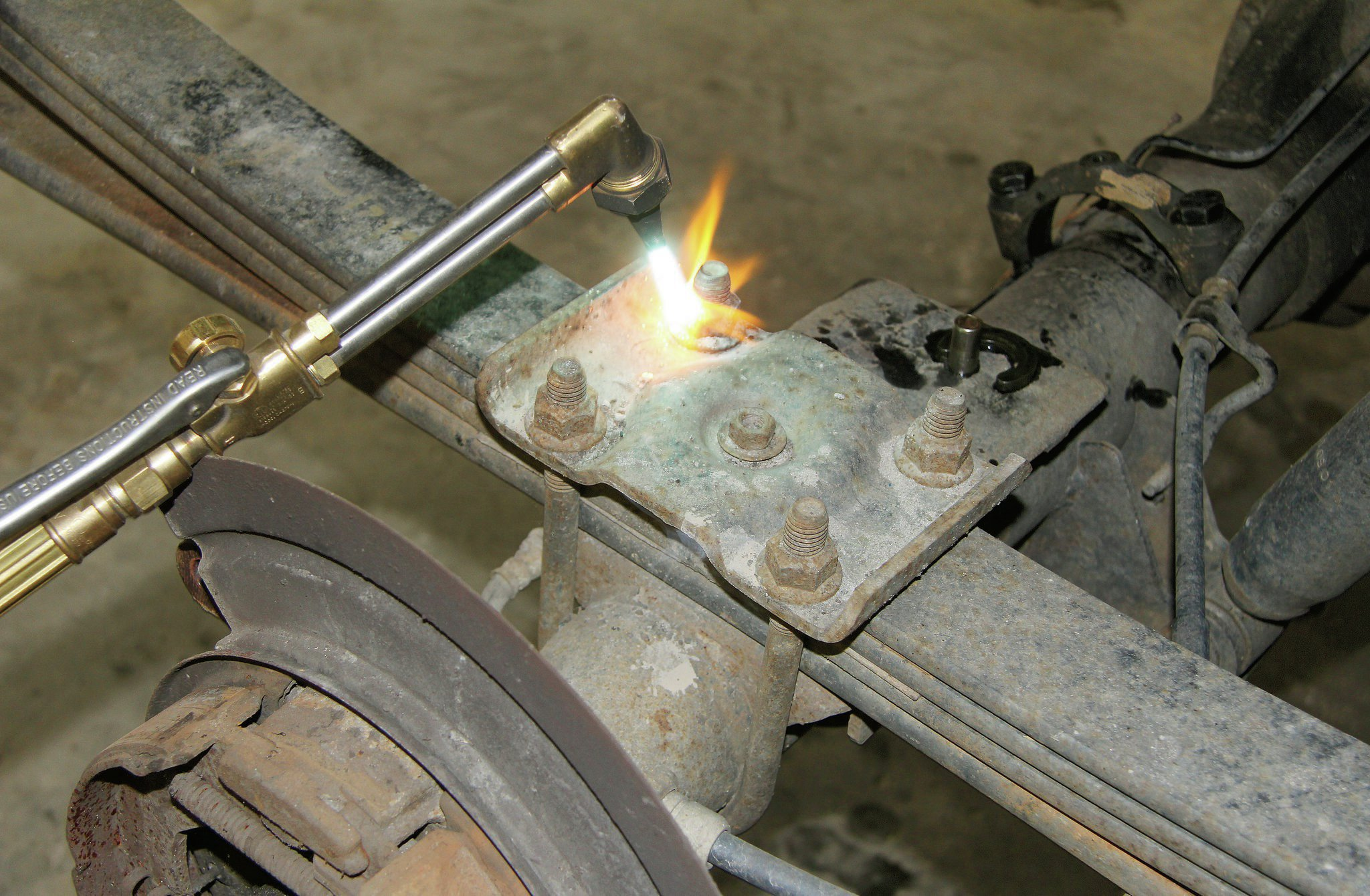 Kill it with fire! Heat is your friend when it comes to breaking free a rusty nut or seized bolt. A small butane torch will usually get the job done, but we like an oxy acetylene torch setup in case we have to cut off the offending member.