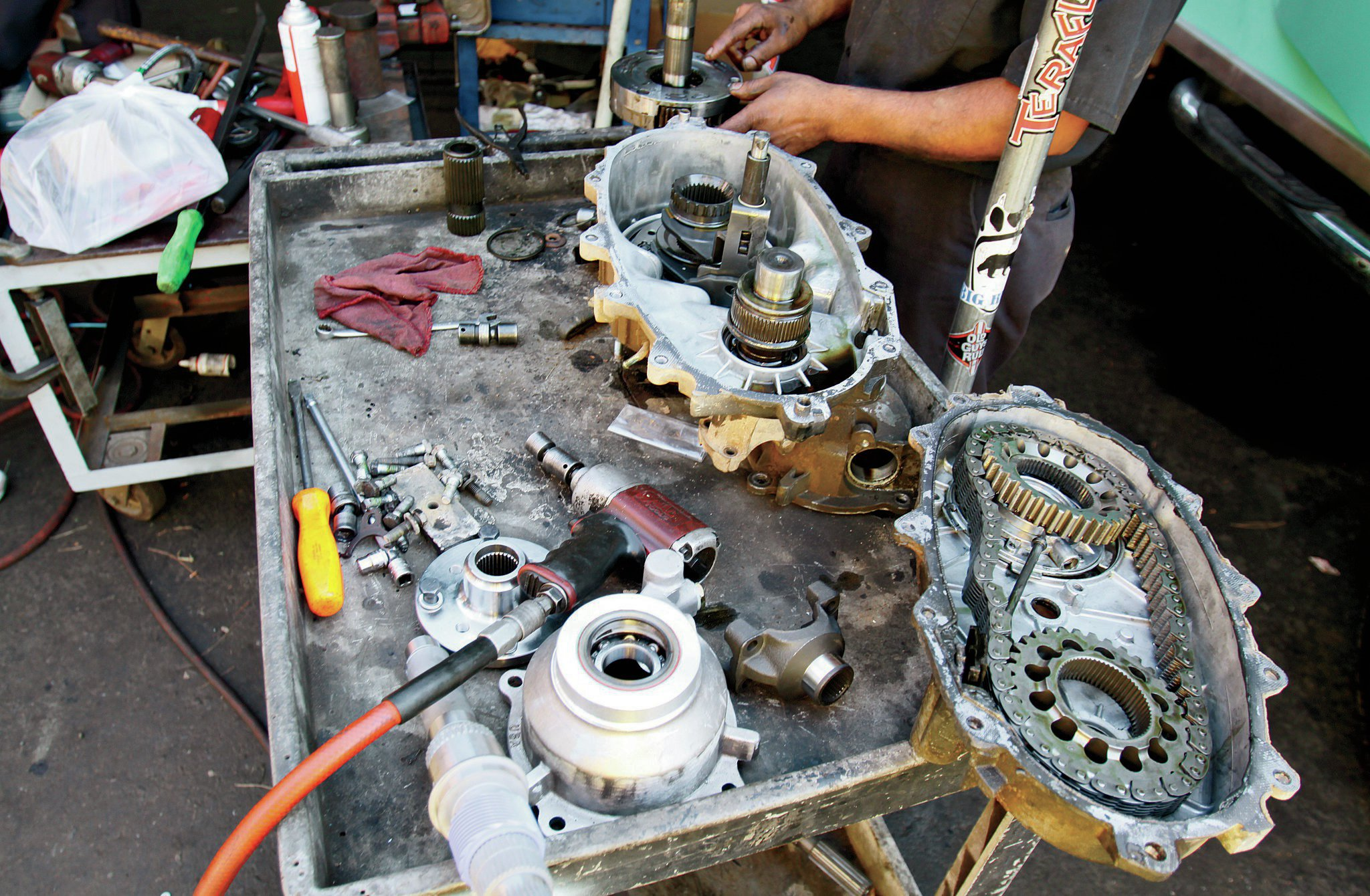 For disassembly of the main case, it is more of the same. Remove all the bolts, and prying as gently as you can, separate the 'case halves. Once you've done that, you can lift the chain and gears straight up off the front and rear output shafts. Then it is time to pull the old mainshaft.
