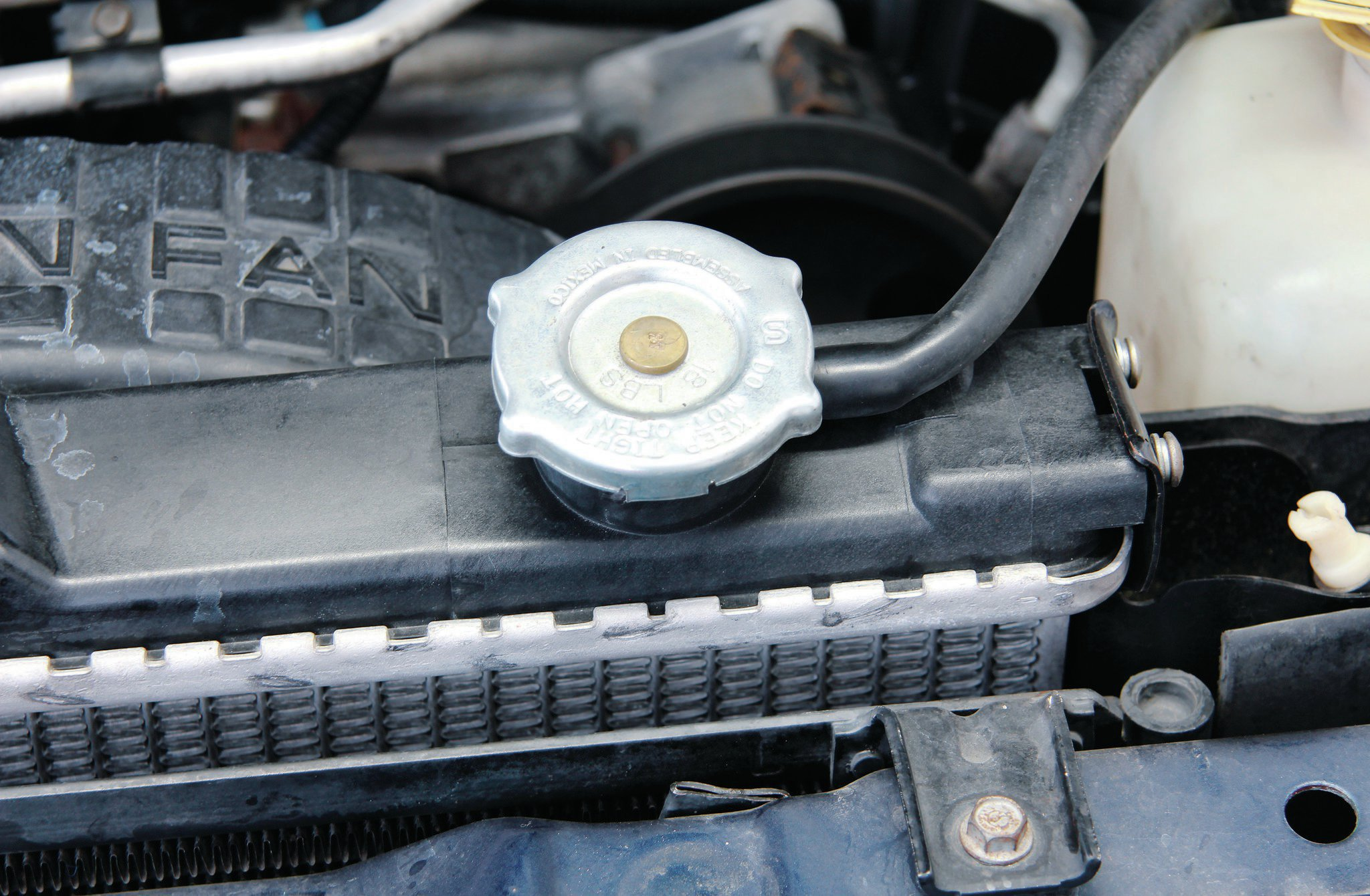 Look at the top of the radiator closely. From the factory, TJs use an aluminum radiator with clamped-on plastic tank caps. These are commonly known to separate and leak. Typically, you'll need to replace the entire radiator when this happens.