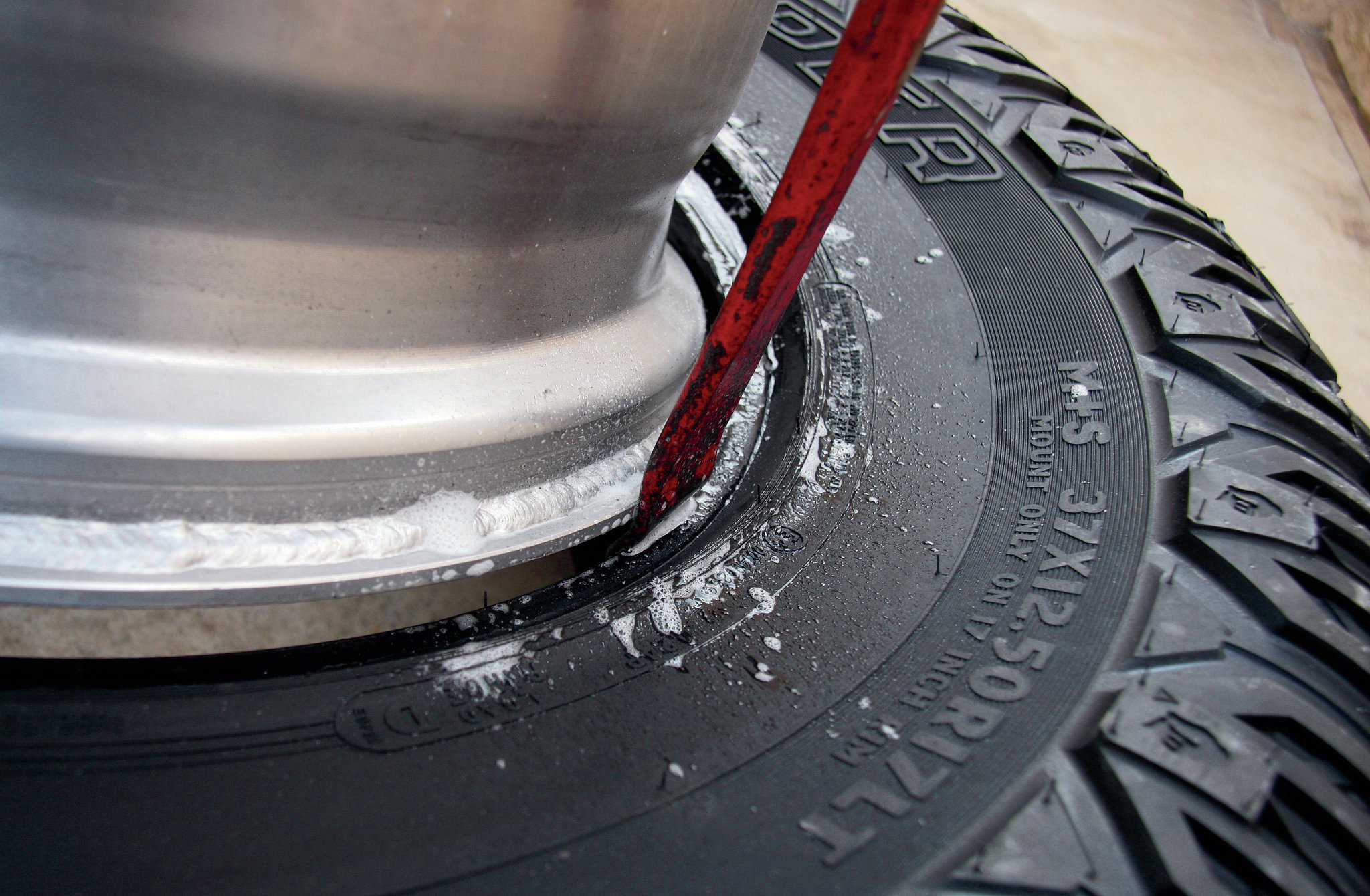 Many tire shops won't dare touch beadlock wheels due to liability fears of drivers using them on public roads. However, it's easy enough to mount tires at home. The front wheel face can easily be slipped inside a tire using a little soapy water and a pry bar. Once there, you simply flip the wheel and tire over, and prepare to bolt the outer ring onto the wheel. Airing up the freshly mounted tire is easy too, generally only requiring pulling the tire toward the rear wheel bead while adding air until the tire pops fully onto the rear bead.