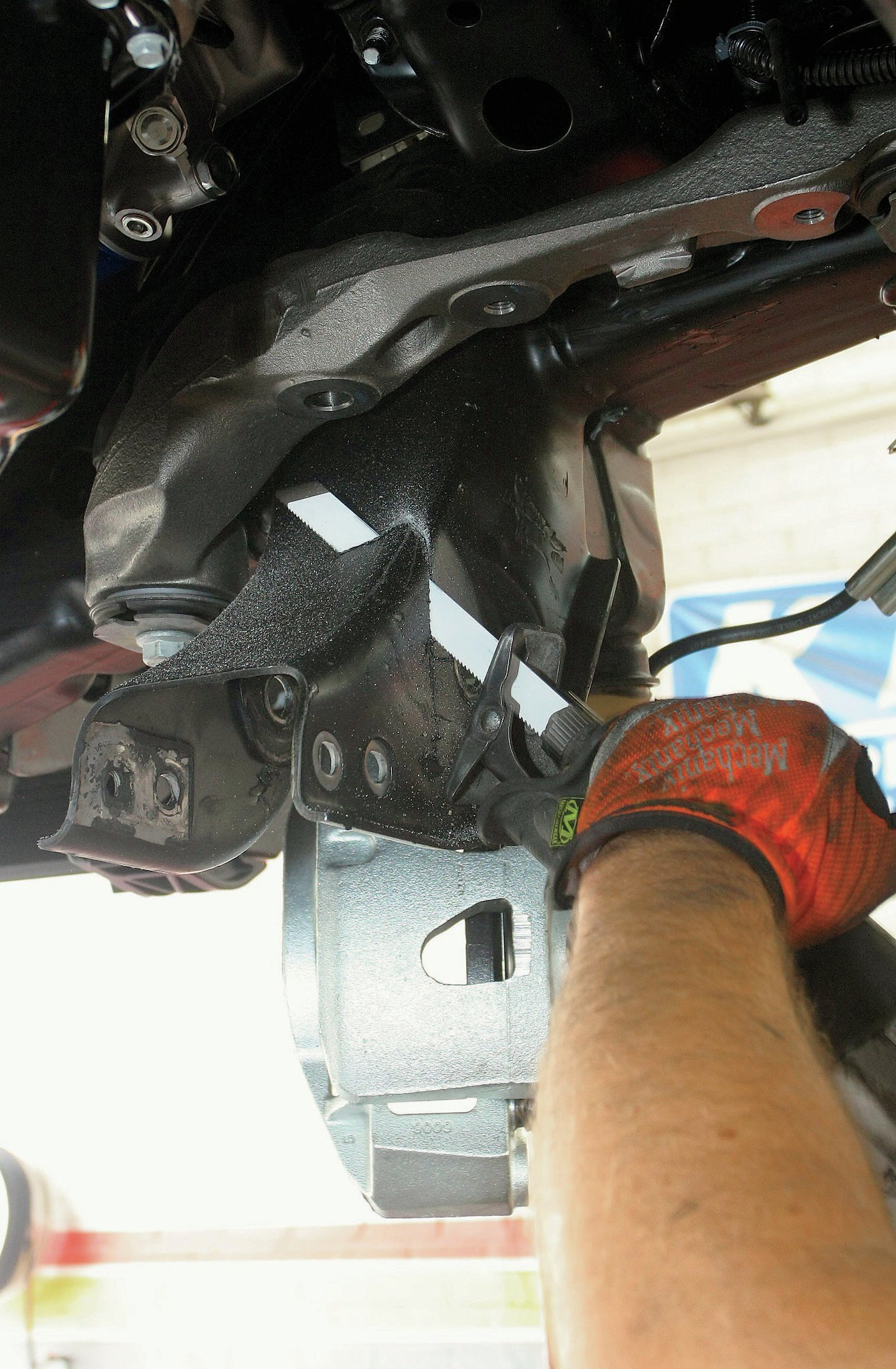 A reciprocating saw is used to modify the rear lower control arm frame pockets.