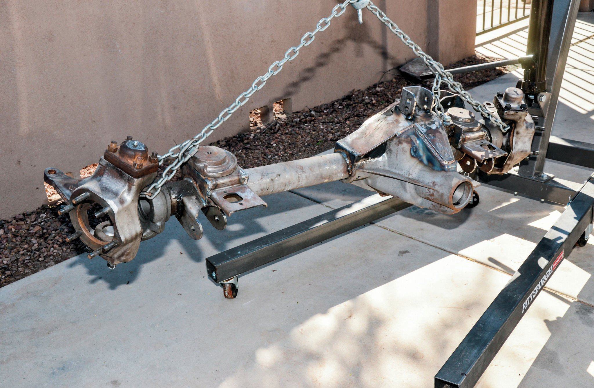 Once the suspension was cycled and flexed, we pulled the front axle. We needed to take the axle back to Rob Bonney Fab for some more TIG welding to the Dana 60 cast steel housing. The axle is starting to get heavy so we used our engine hoist to move the axle out of the garage and into the back of our truck.