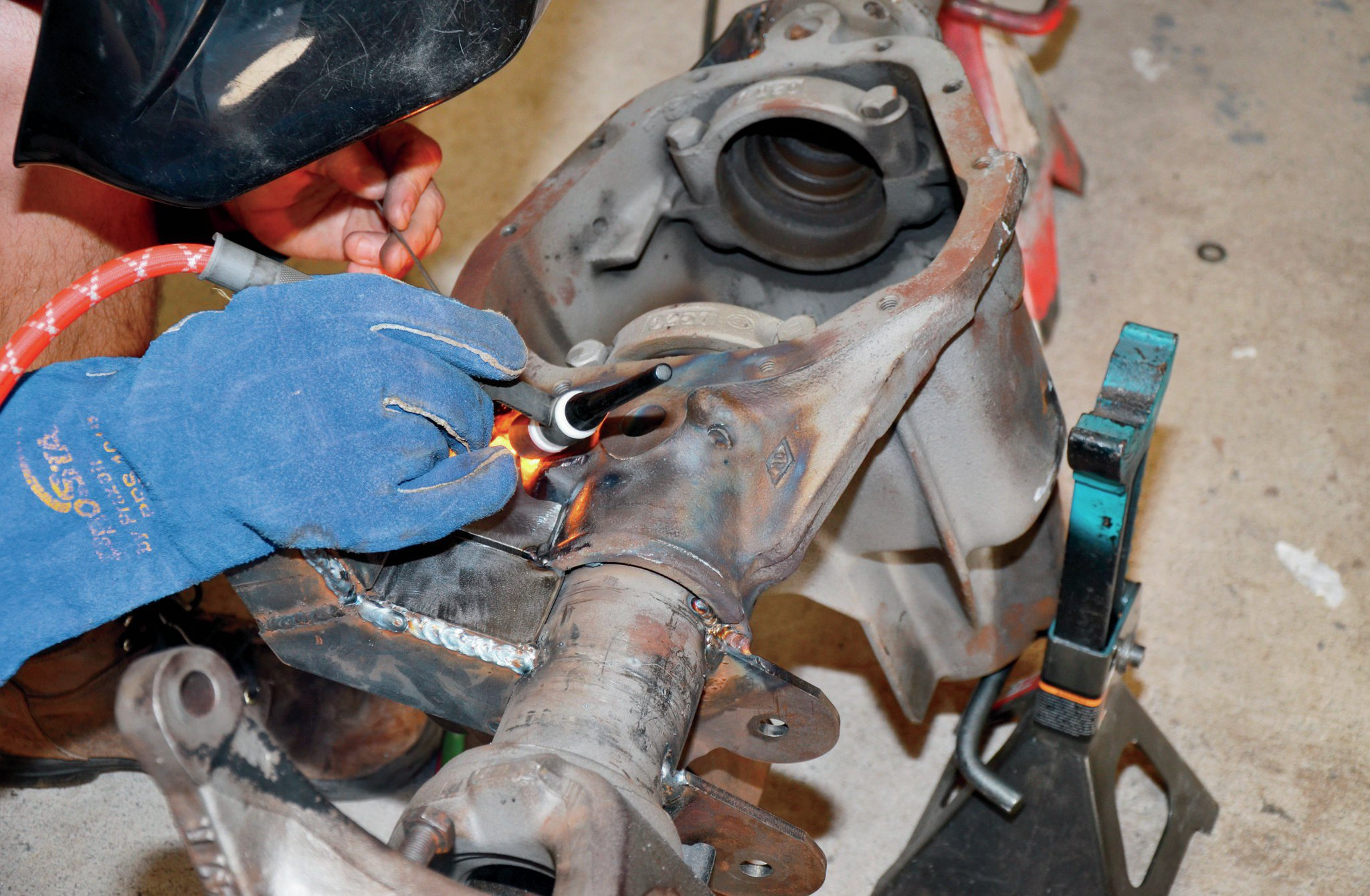 Once the fill plate was in hand, Bonney started pre-heating the Dana 60 cast steel housing with an oxy-acetylene torch. Once properly heated, Bonney TIG welded our plate steel brackets to the casting using special rod he has used in the past. This is not the world's strongest method of welding, but with plenty of surface area joining the cast steel to the plate, we can be sure that our low-slung Jeep will stay together come what may. Once the TIG work is complete, post-heating the casting is necessary to prevent the axle from cooling too quickly.