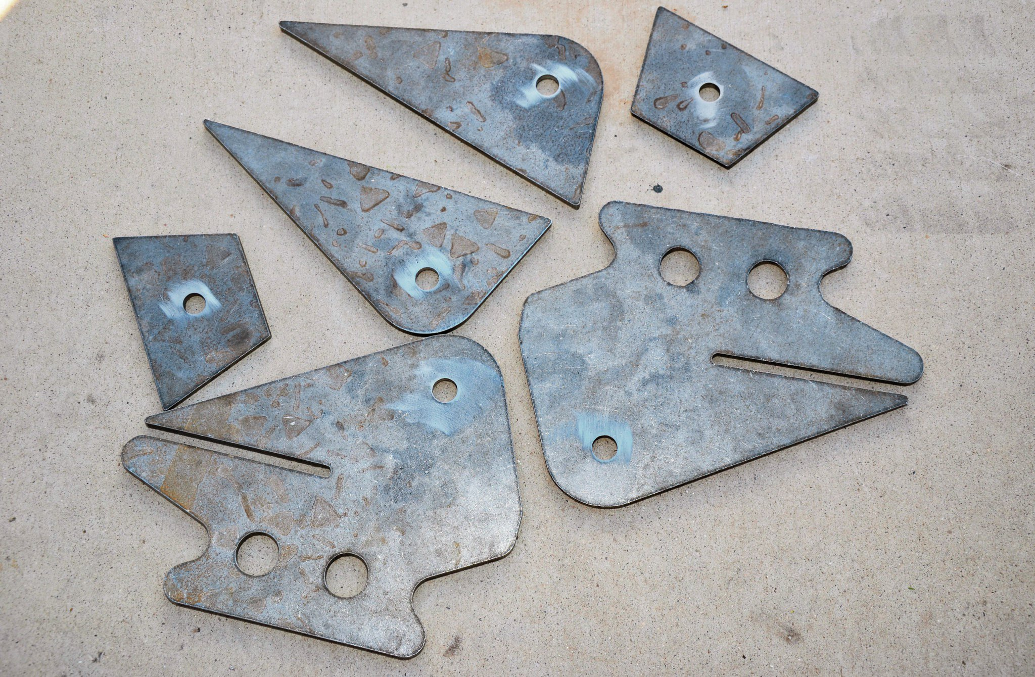 Here are some other brackets they were working on for a different project at Rob Bonney Fab. These are for a solid-axle conversion on a Chevy, so it's not so applicable to us. However, it shows the range of what can be cut, including fish-mouthed frame plates and mounting holes. Add in some work with a metal brake and you can have almost anything you can imagine pre-built and ready to weld in place. Sure, you could do this with a metal band saw, plasma cutter, or the like, but it would take forever and not look nearly this clean.