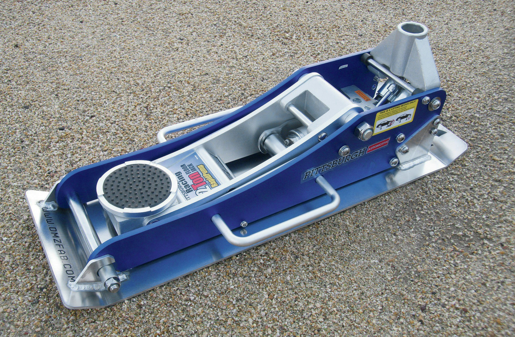 On a lot of IFS and long-travel vehicles, it's not uncommon to carry a hydraulic floor jack. This is especially true on race rigs. These jacks can often go very low in height and have substantial jack height ranges. The aluminum ones are more expensive but considerably lighter than the steel versions, and the weight savings is welcome on an off-road rig. This is a Harbor Freight aluminum racing jack. These have proven themselves to offer good quality and value for weekend warriors. The sand skid is from DMZ Fab and replaces the stock wheels so the jack can be more easily maneuvered in the dirt.