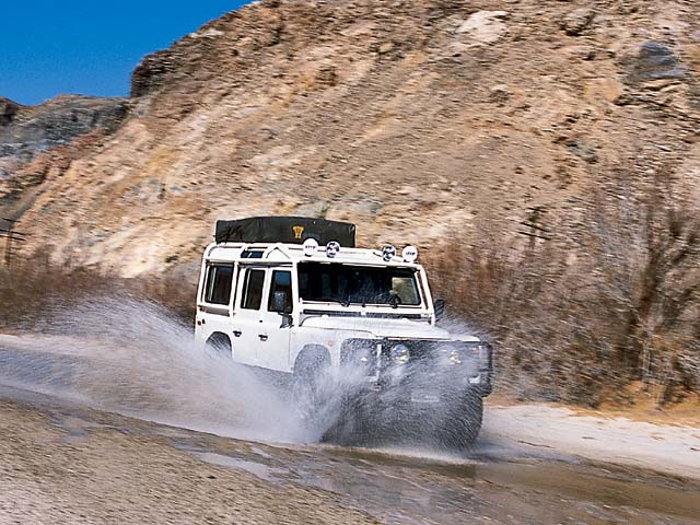 Brett Carnot blasts though a water crossing in his NAS 110 Defender.